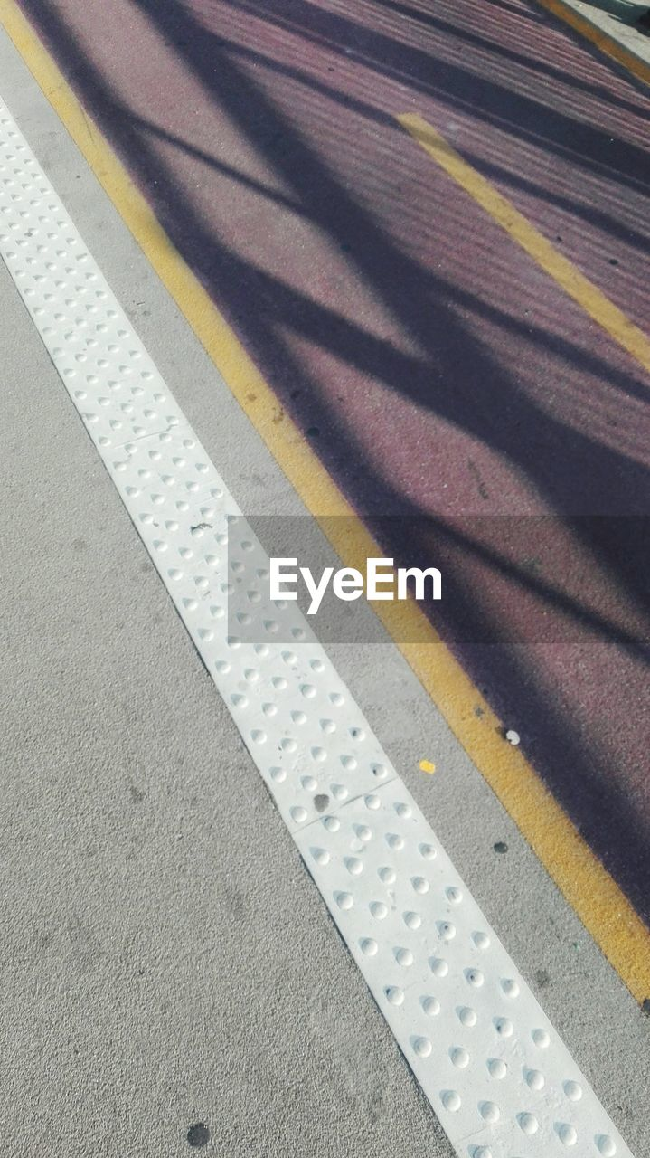 transportation, high angle view, no people, yellow, pattern, road marking, road, day, close-up, marking, symbol, indoors, sign, rail transportation, public transportation, railroad station platform, sunlight, asphalt, city, dividing line