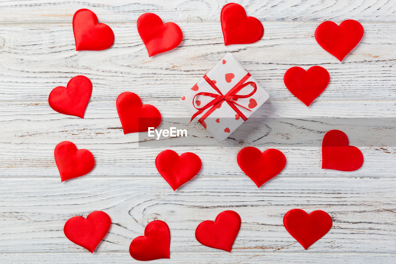 red, heart shape, love, positive emotion, wood - material, emotion, indoors, creativity, shape, design, table, still life, art and craft, no people, decoration, close-up, directly above, craft, white color, high angle view