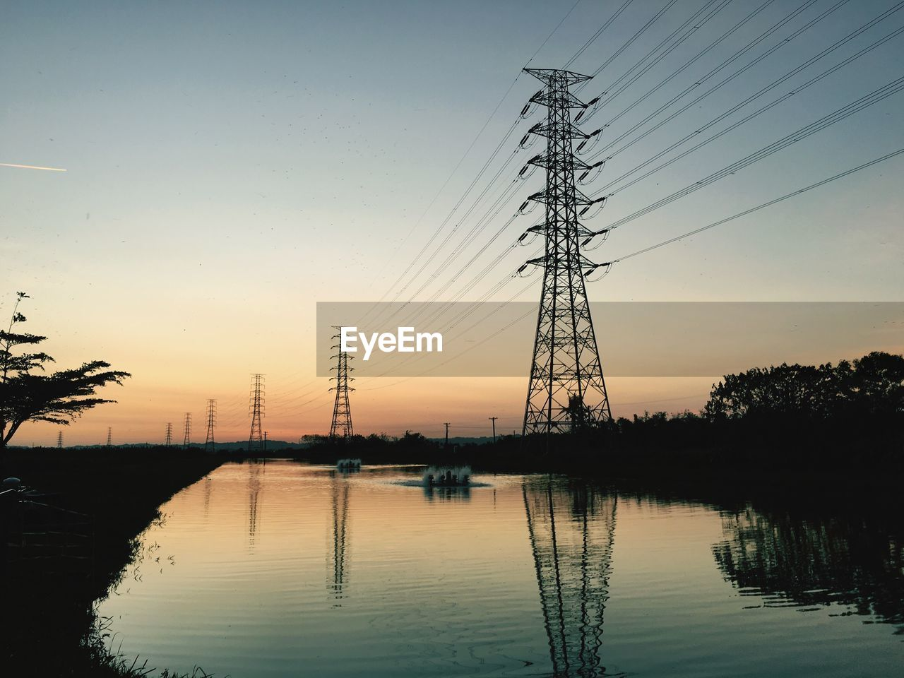 sunset, electricity pylon, cable, connection, sky, no people, silhouette, power line, reflection, water, tree, electricity, fuel and power generation, outdoors, nature, scenics, beauty in nature, clear sky, day