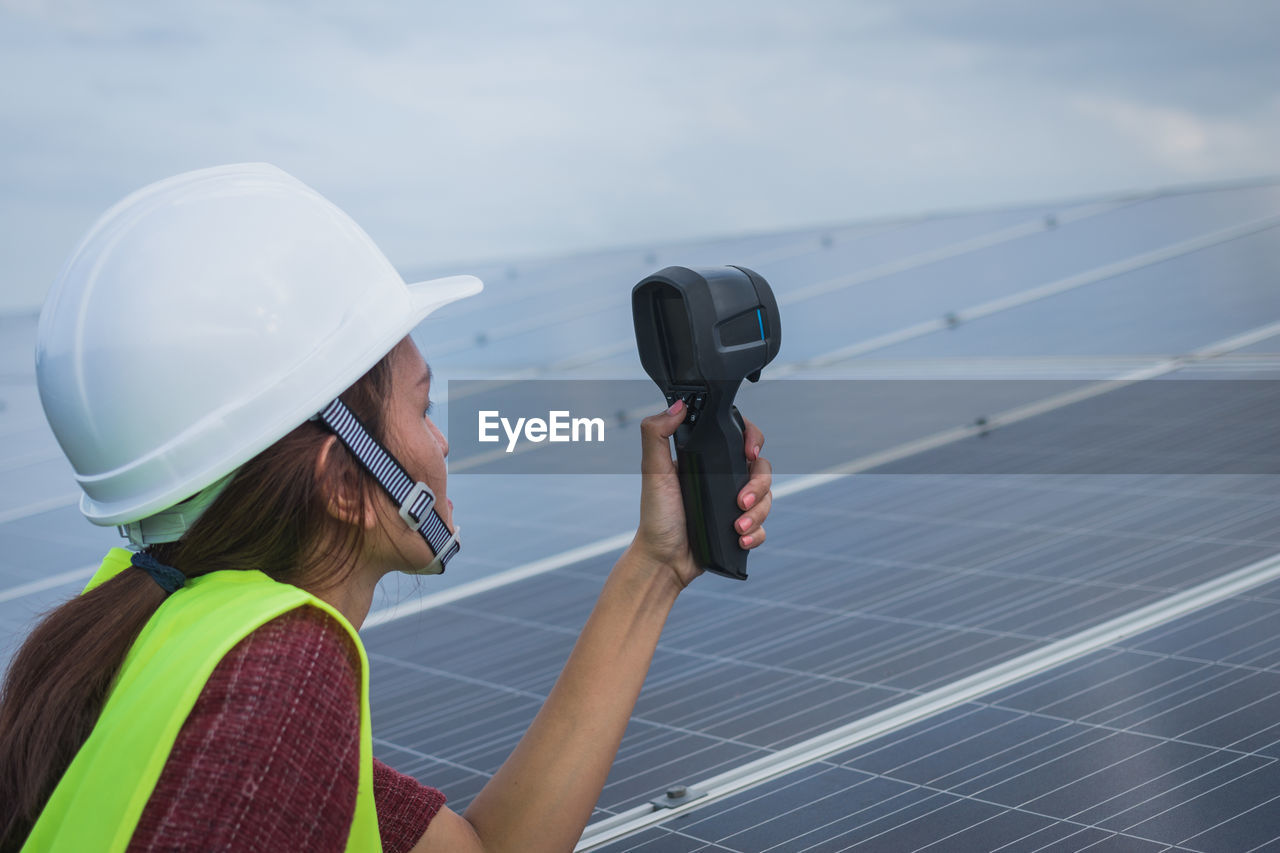 one person, renewable energy, sky, adult, real people, nature, environmental conservation, alternative energy, technology, day, hat, women, occupation, helmet, fuel and power generation, solar energy, headshot, environment, focus on foreground, water, outdoors, electricity, power supply