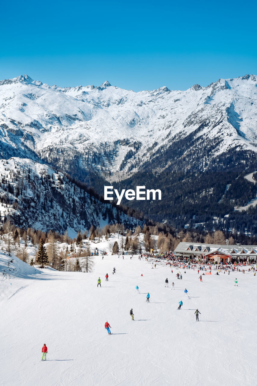 People Skiing Against Snowcapped Mountains