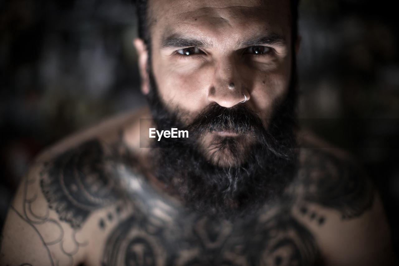 Portrait of beard man wearing nose ring indoors