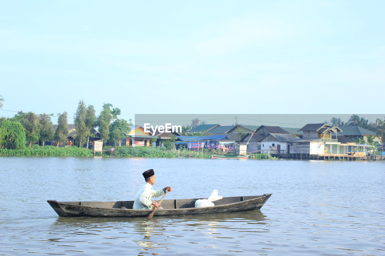 water, nautical vessel, transportation, mode of transportation, real people, one person, waterfront, nature, lifestyles, sky, day, built structure, lake, architecture, building exterior, leisure activity, men, oar, outdoors