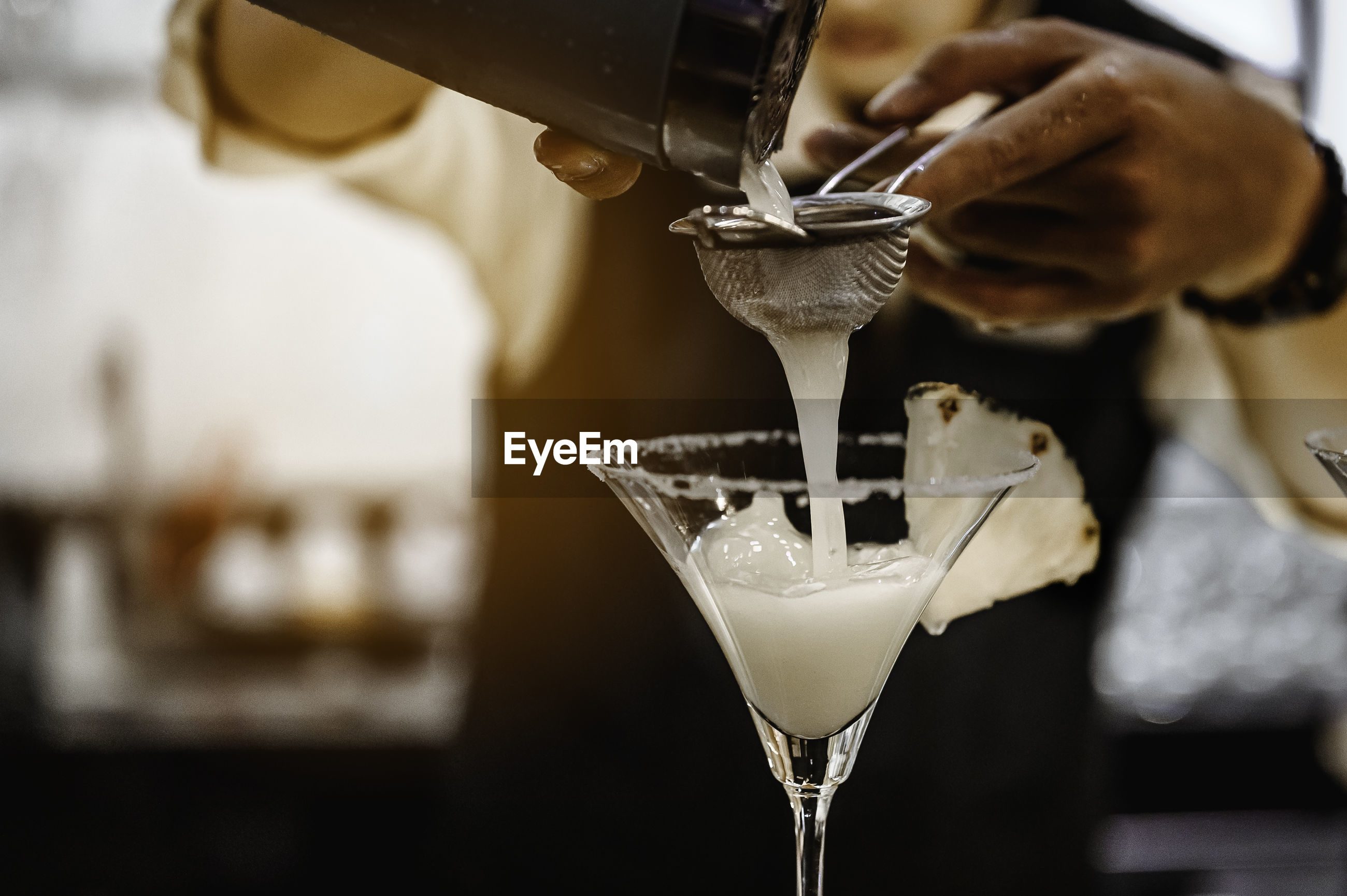 Close-up of cocktail pouring in glass at bar counter