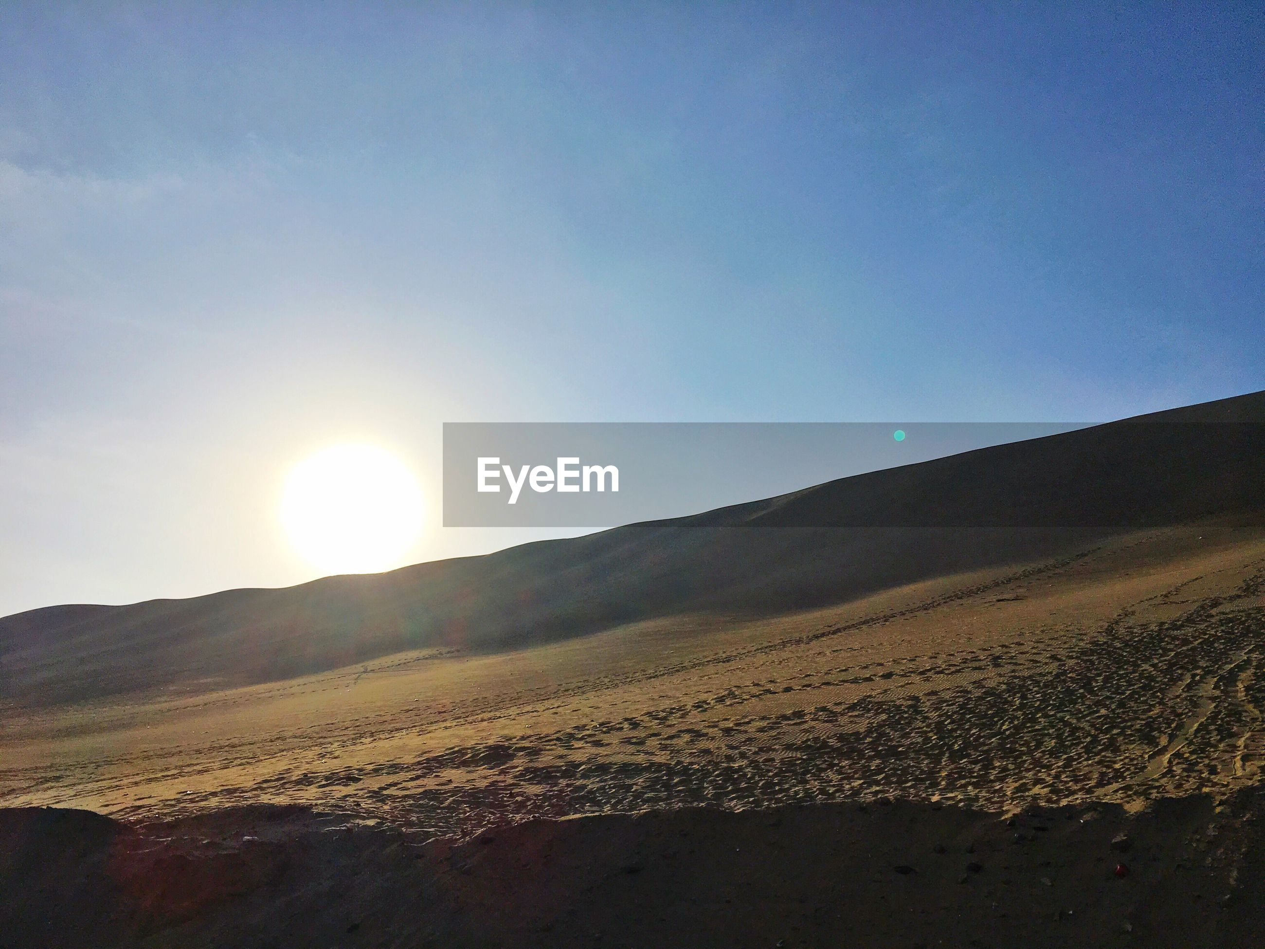 Low angle view of arid landscape against sky on sunny day