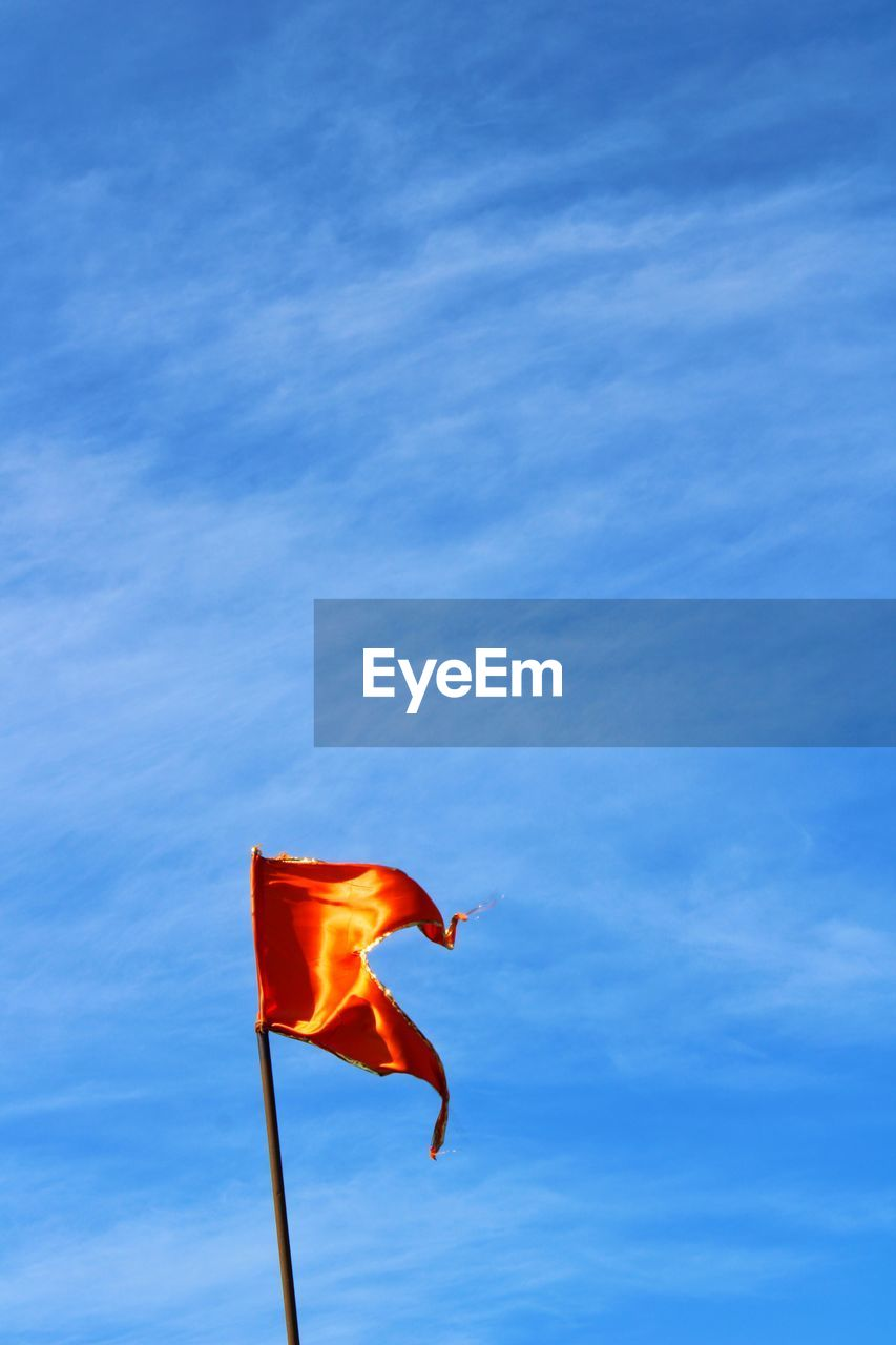 sky, flag, nature, cloud - sky, blue, low angle view, environment, red, no people, day, patriotism, orange color, wind, motion, outdoors, flying, mid-air, beauty in nature, sunlight