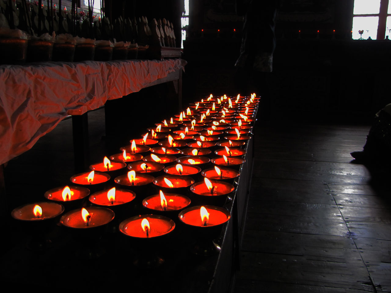 heat - temperature, flame, burning, candle, in a row, orange color, glowing, illuminated, indoors, large group of objects, arrangement, no people, spirituality, night