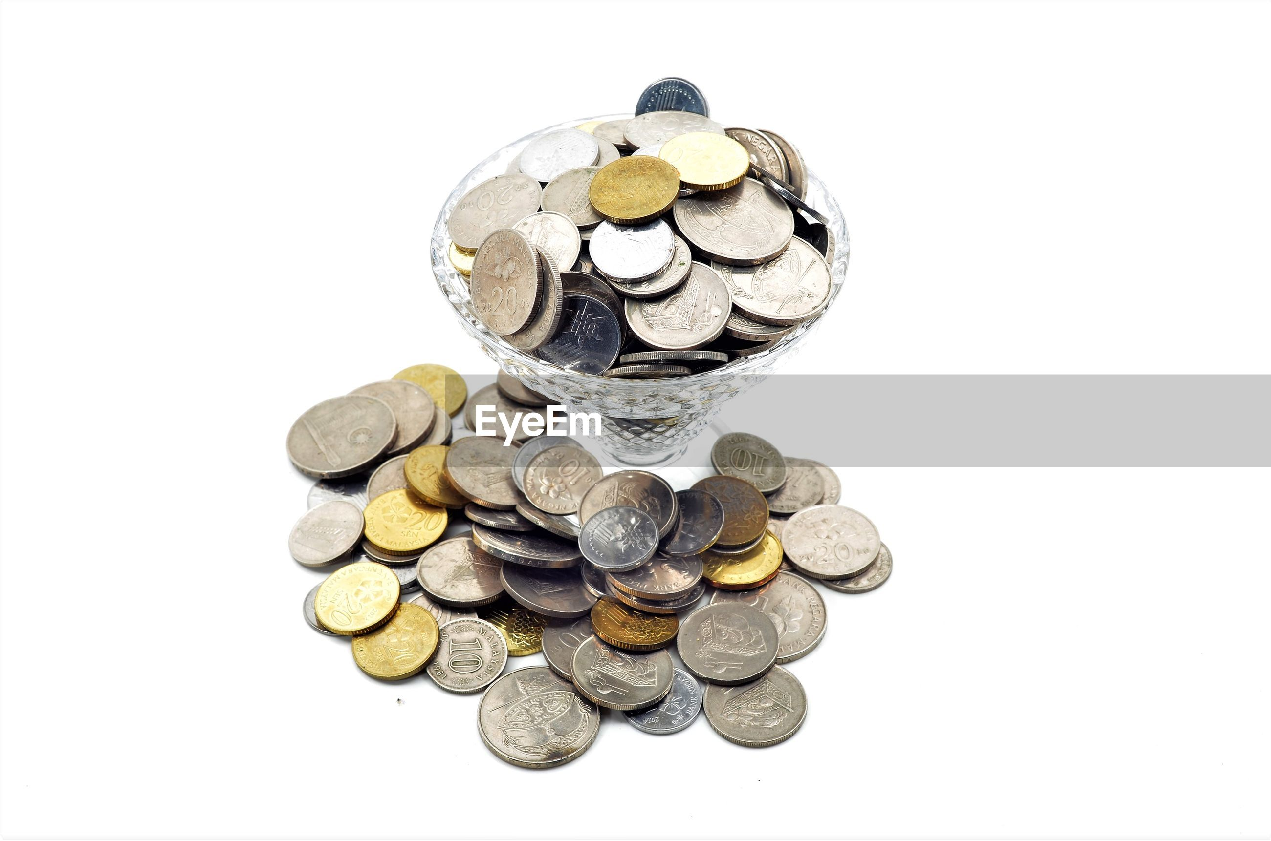 High angle view of coins in glass on white background