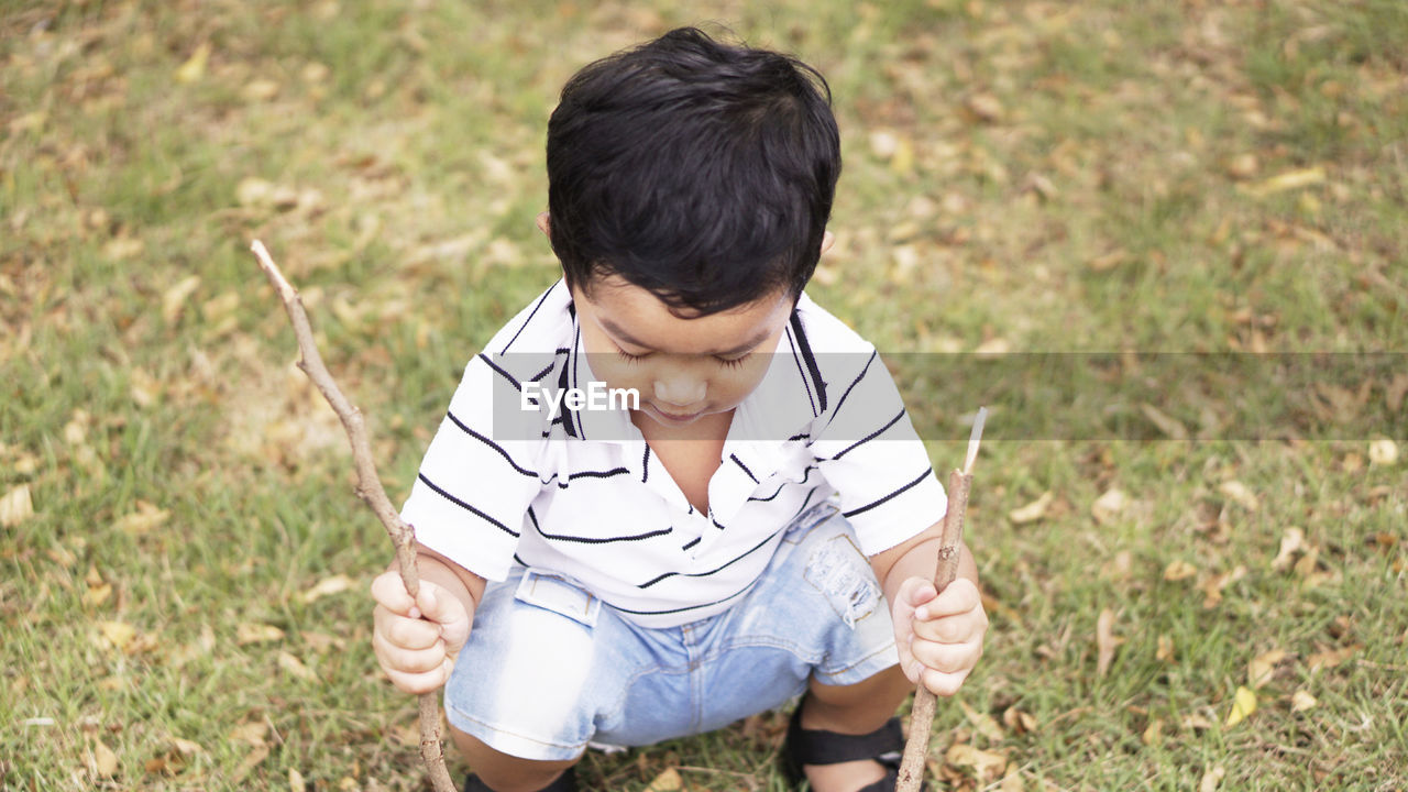 casual clothing, grass, one person, lifestyles, real people, leisure activity, high angle view, field, land, day, nature, three quarter length, plant, front view, child, boys, focus on foreground, looking, childhood, outdoors, teenager, innocence