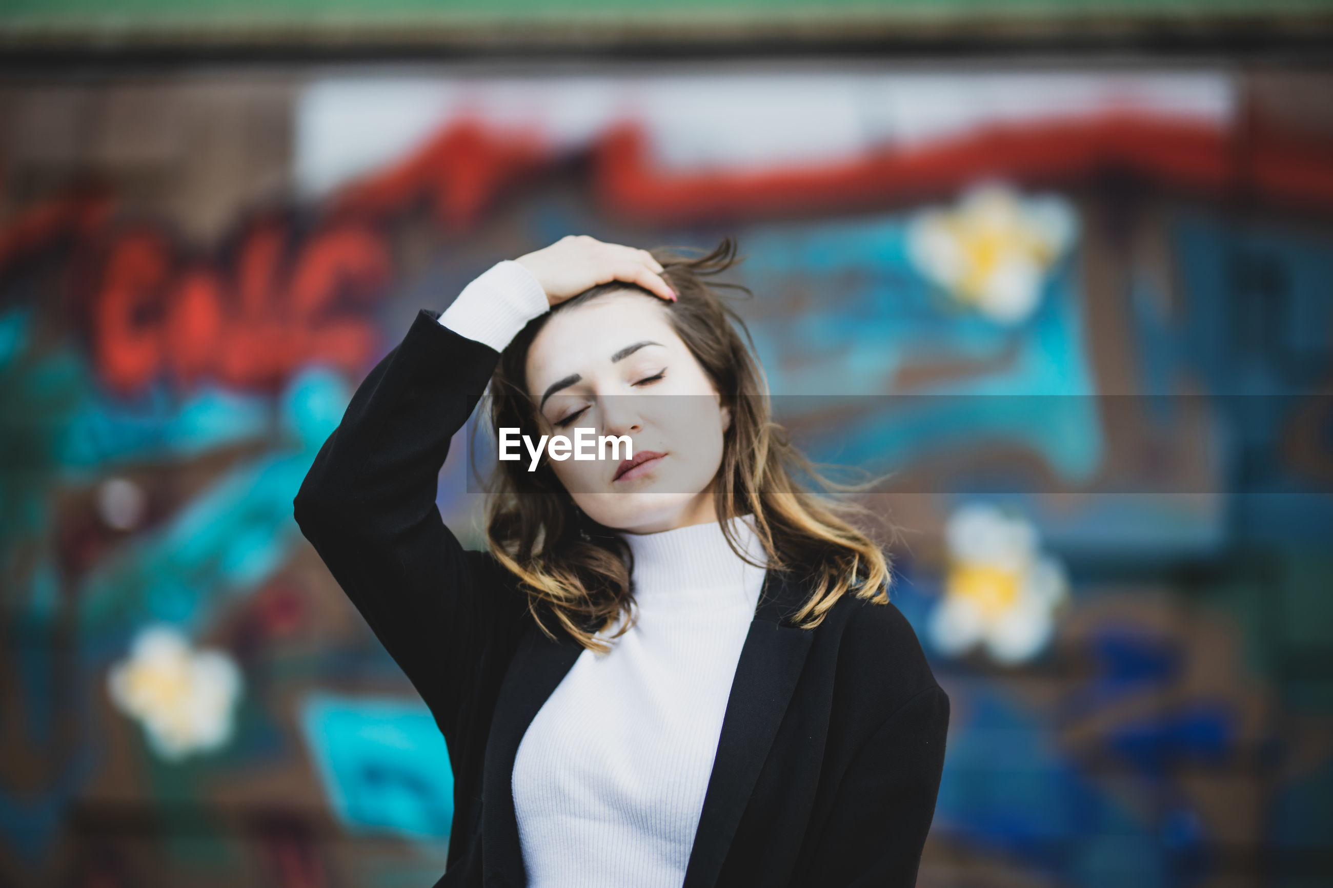 Beautiful young woman with eyes closed standing against wall in city