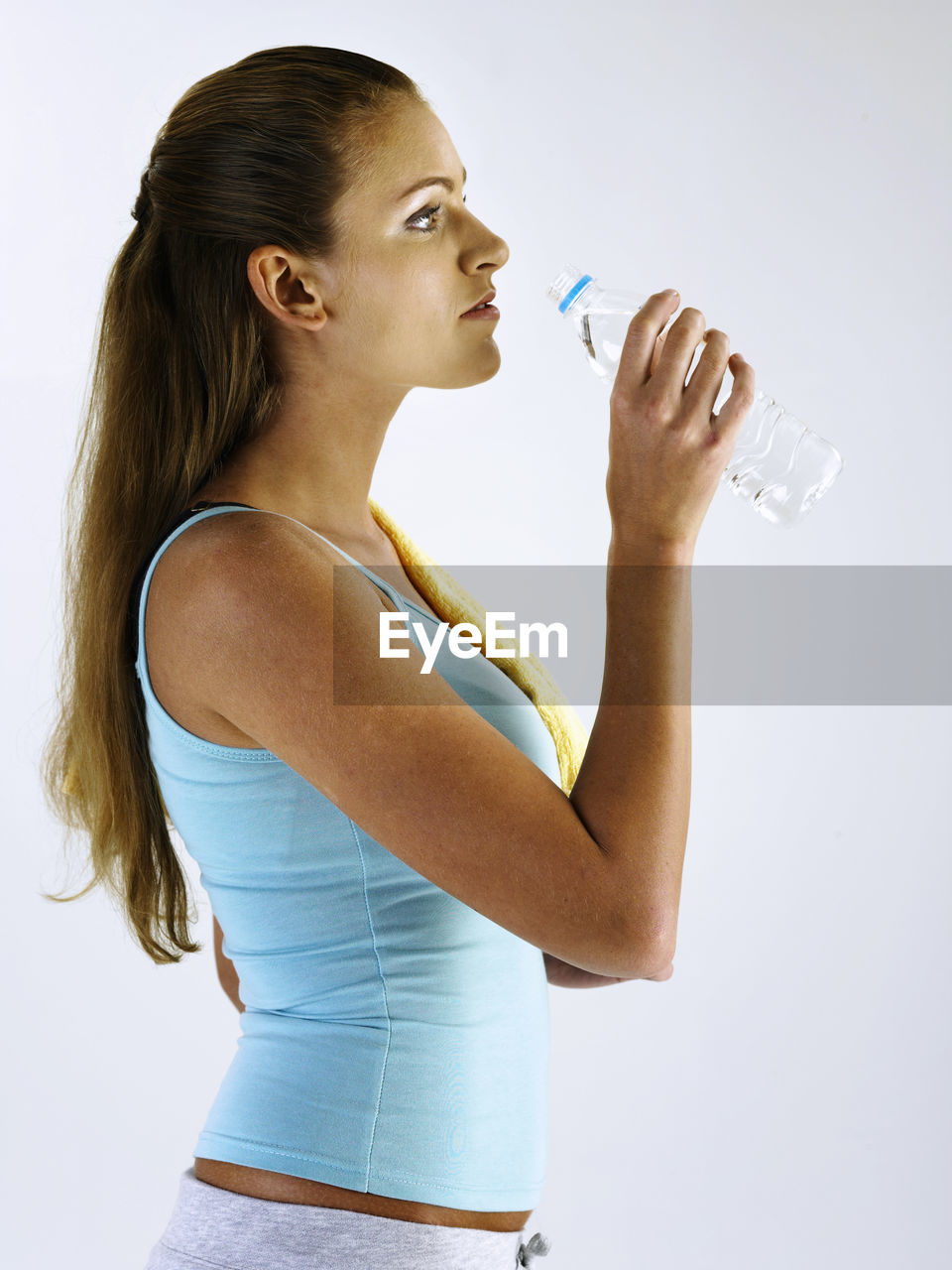 Profile view of woman drinking water against white background
