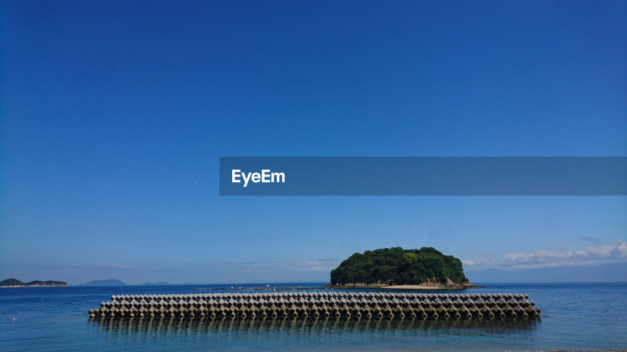water, sky, sea, blue, copy space, scenics - nature, clear sky, beauty in nature, tranquil scene, tranquility, waterfront, nature, no people, idyllic, day, land, plant, non-urban scene, tree, outdoors