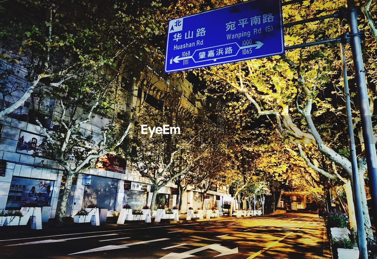 sign, tree, plant, communication, city, building exterior, road, text, architecture, street, transportation, information, built structure, information sign, road sign, guidance, symbol, nature, script, non-western script, no people, outdoors