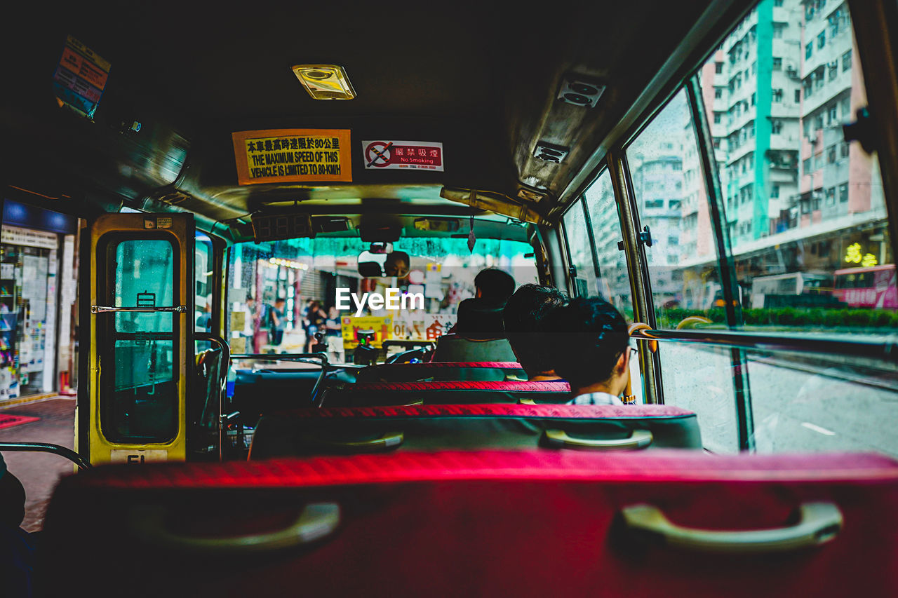 mode of transportation, transportation, public transportation, vehicle interior, real people, land vehicle, men, group of people, bus, lifestyles, text, women, city, travel, rail transportation, architecture, people, train, seat, window, outdoors