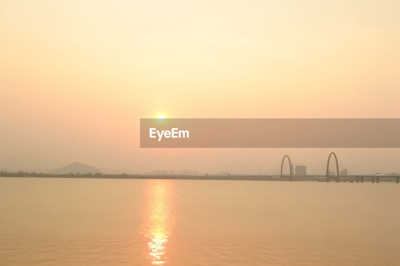 sunset, sun, orange color, reflection, sky, built structure, water, nature, outdoors, beauty in nature, no people, scenics, architecture, sea, travel destinations, clear sky, day