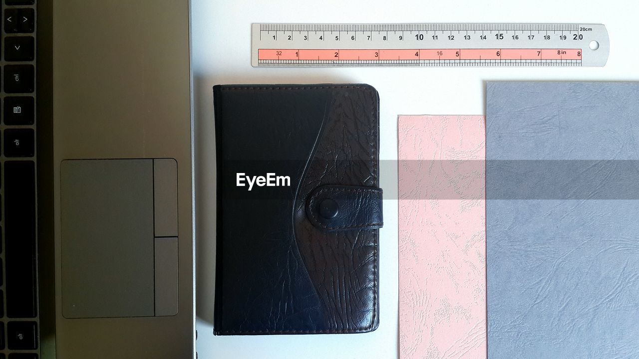 High angle view of ruler and wallet with laptop on table