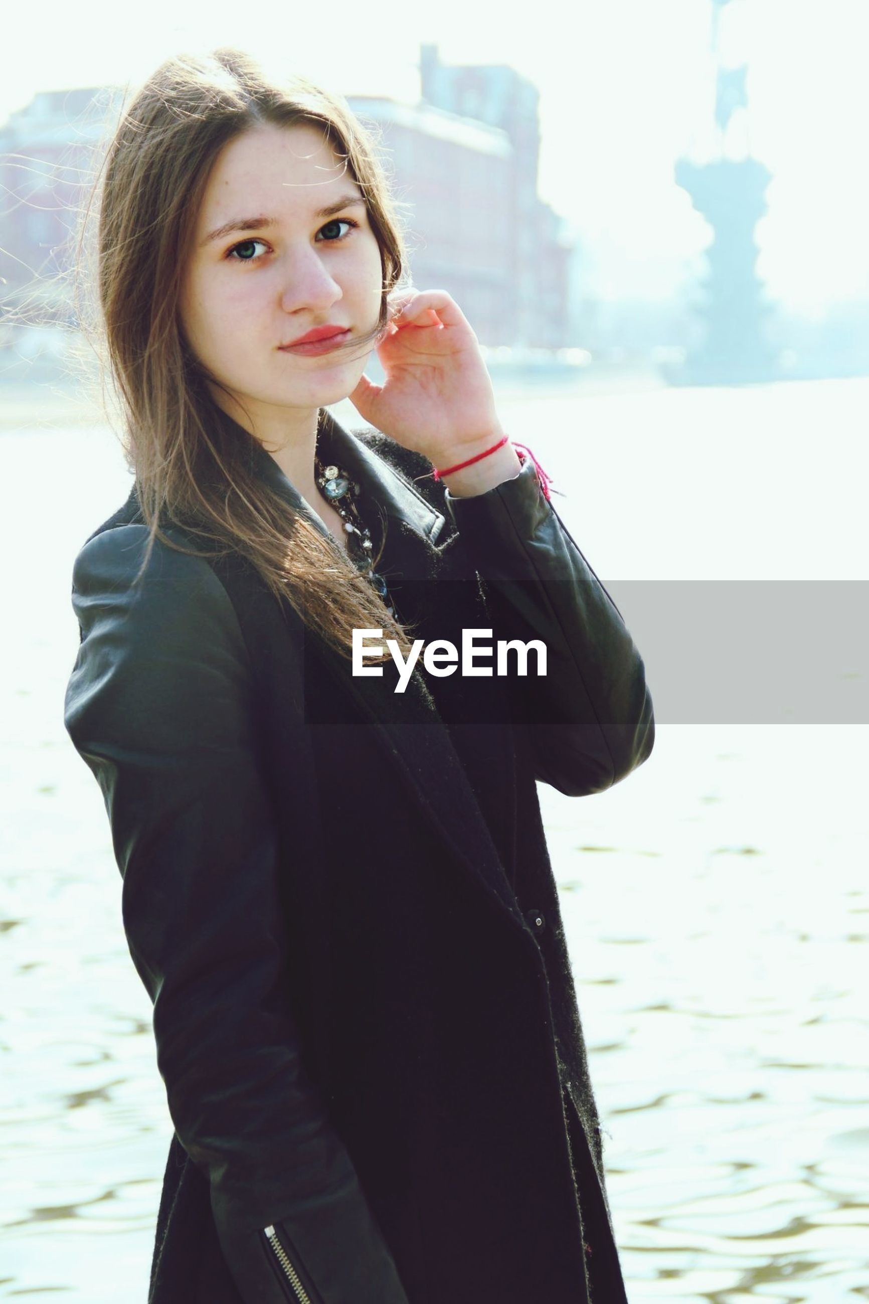 lifestyles, young adult, casual clothing, person, standing, three quarter length, leisure activity, front view, waist up, looking at camera, portrait, focus on foreground, warm clothing, young women, water, smiling, jacket