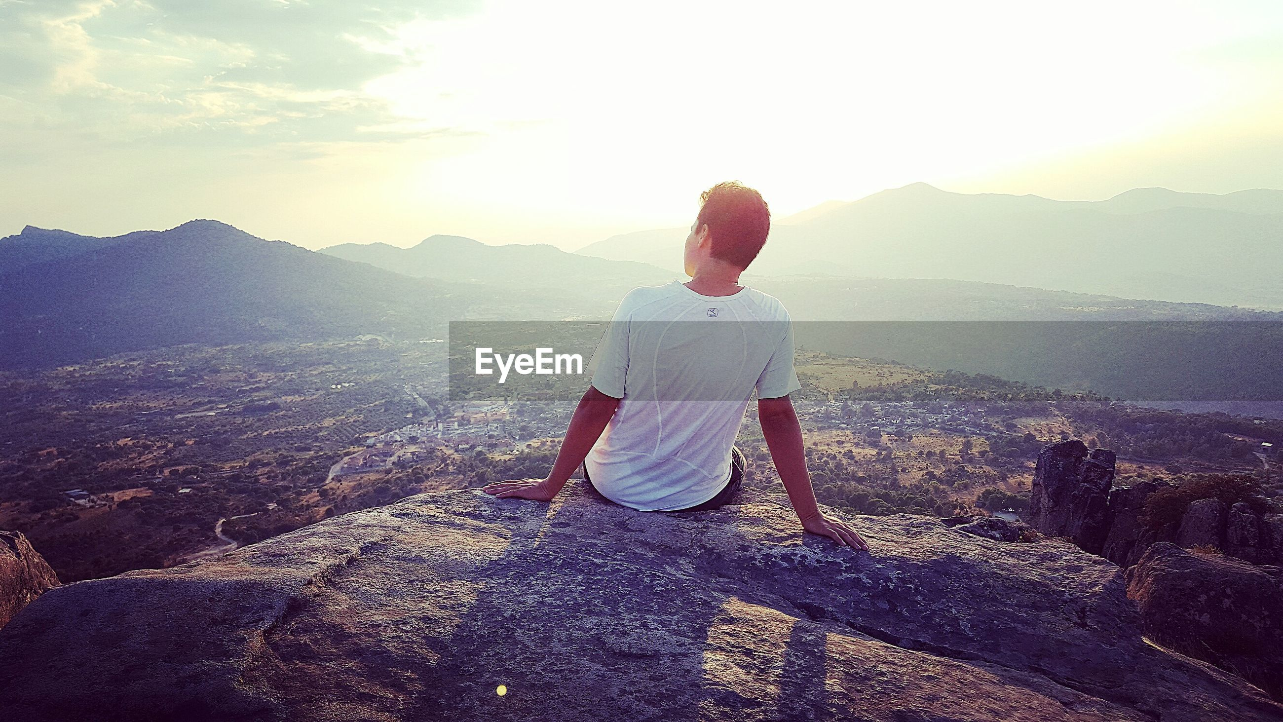 Rear view of man sitting on mountain during sunset