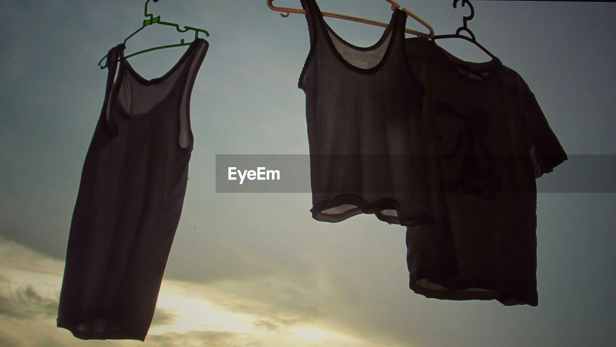 Clothes drying on coathangers against sky