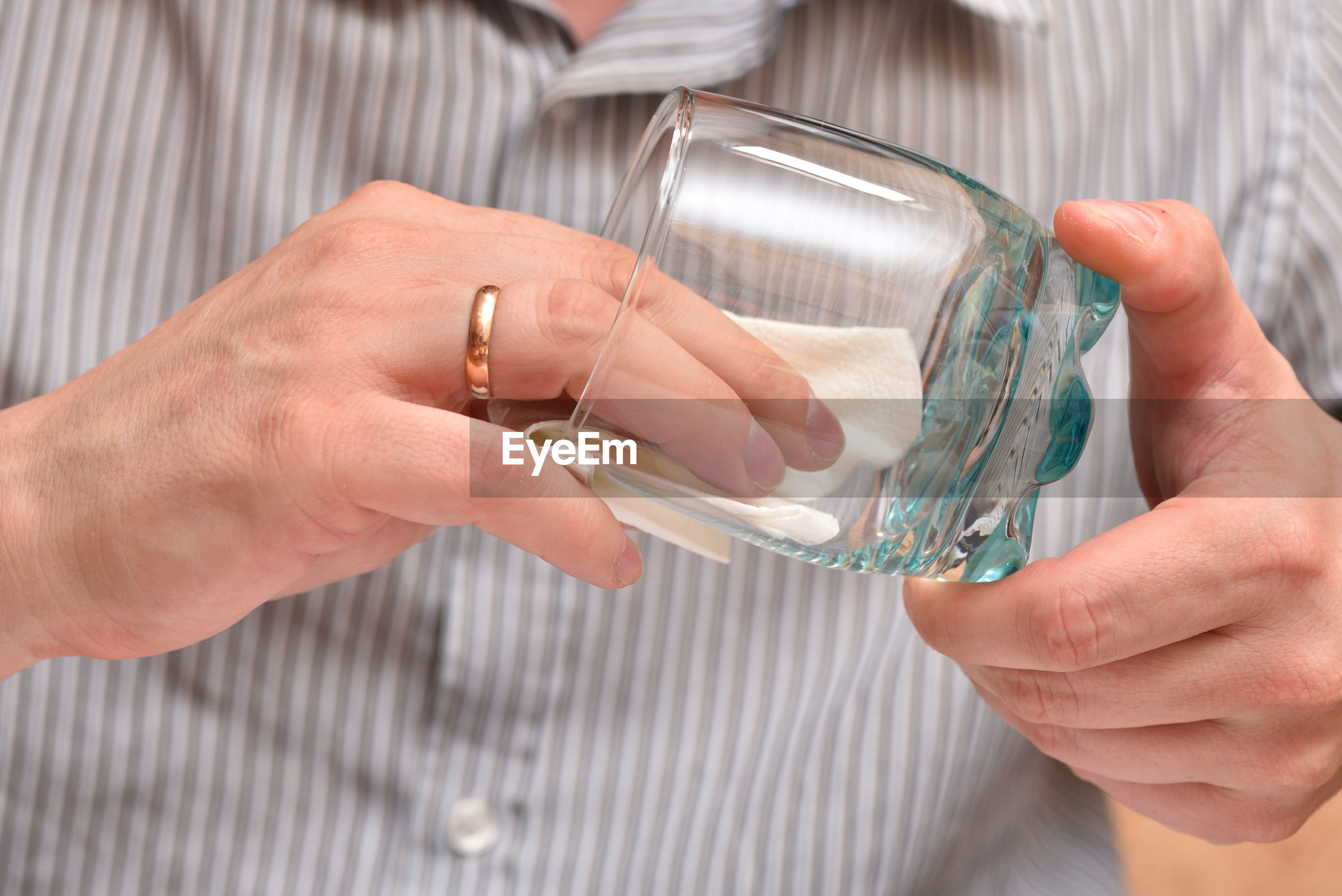 Midsection of man cleaning drinking glass