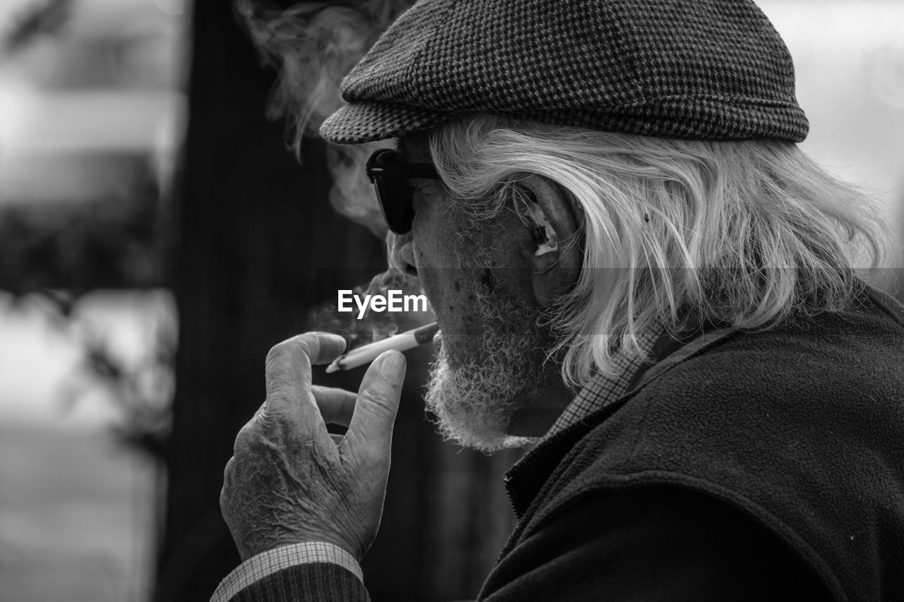 Side View Of Senior Man Smoking Cigarette While Sitting Outdoors