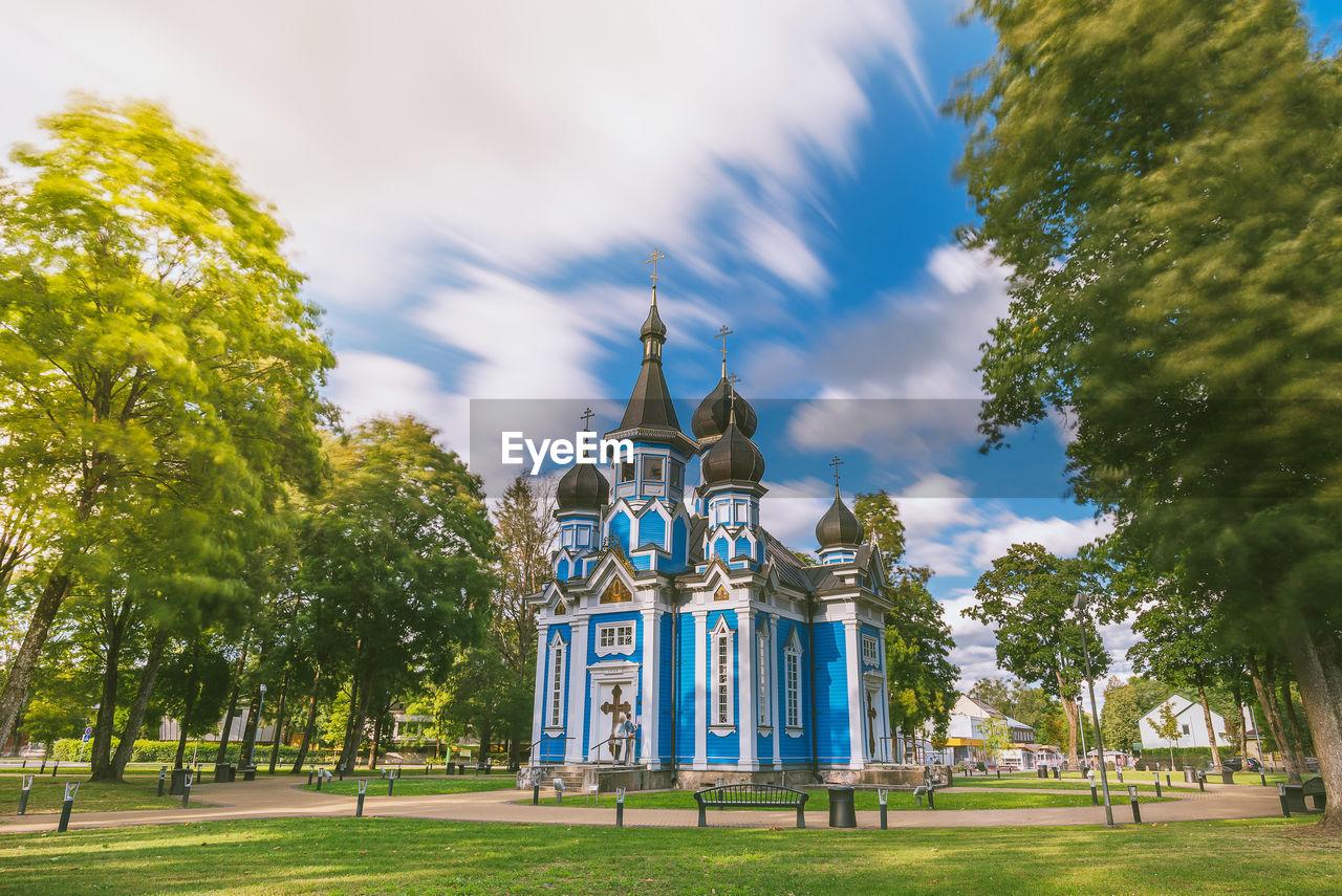 Church amidst trees on field against cloudy sky