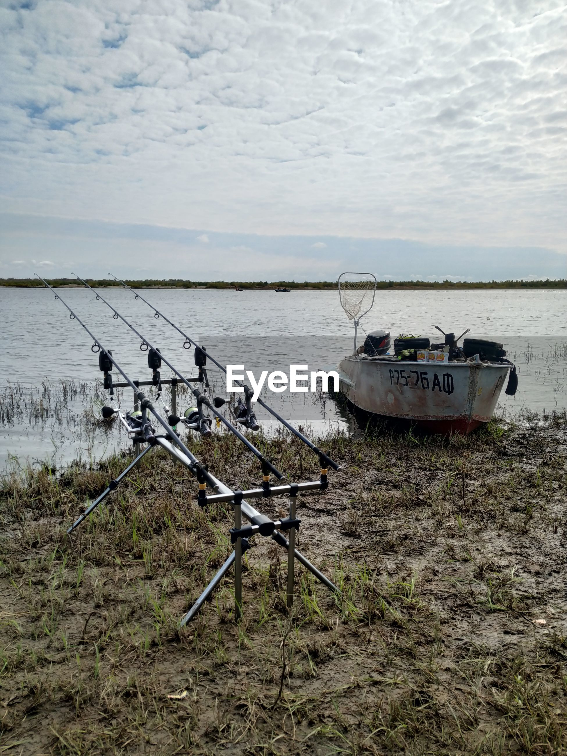 FISHING BOAT MOORED ON SHORE AGAINST SKY
