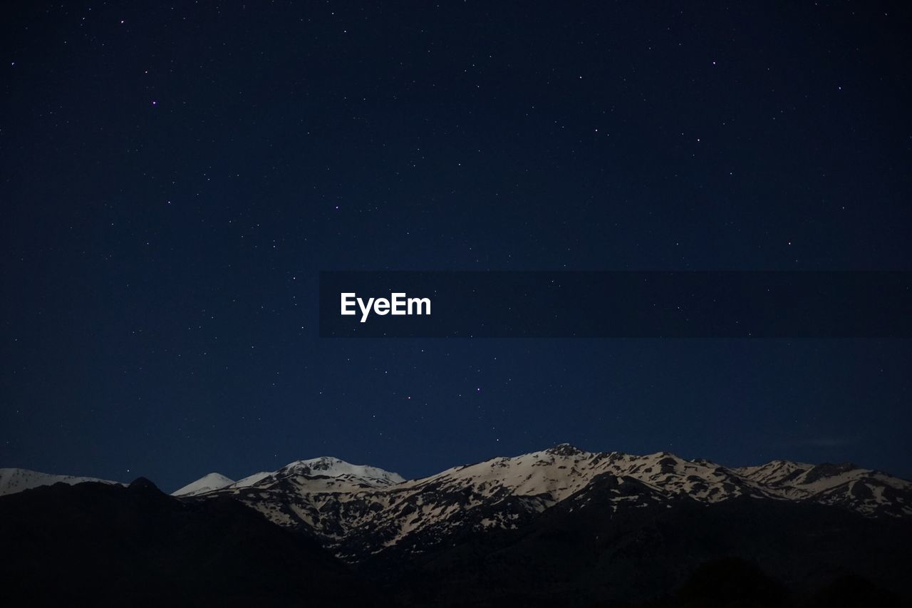 High section of snow covered mountain against clear sky