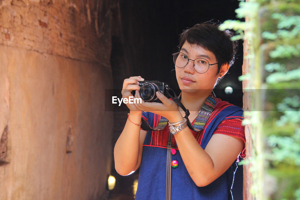 one person, real people, holding, photography themes, camera - photographic equipment, technology, photographic equipment, standing, photographing, front view, lifestyles, glasses, portrait, leisure activity, activity, young adult, waist up, casual clothing, camera, digital camera, photographer, digital single-lens reflex camera, outdoors, slr camera