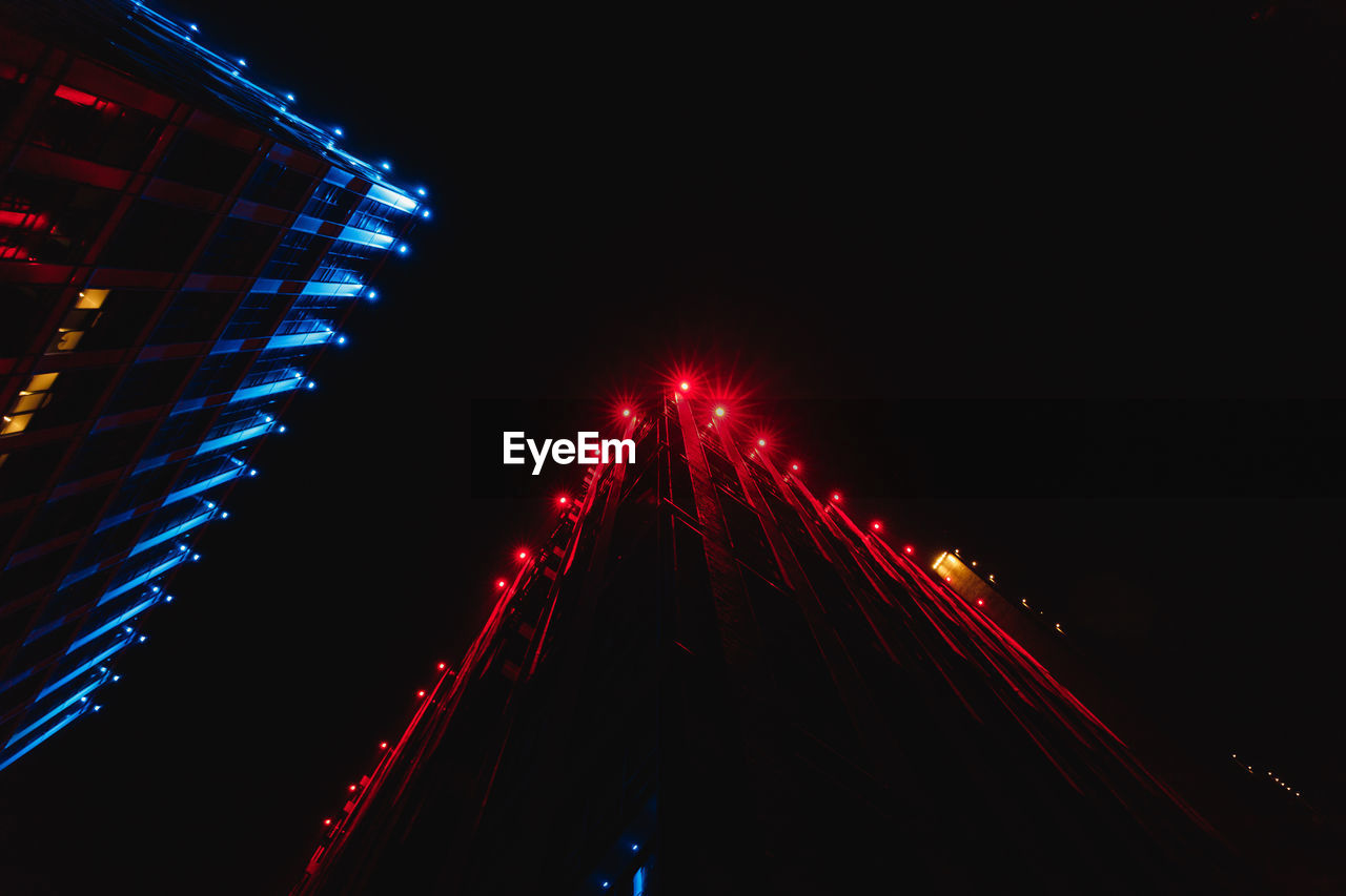 illuminated, night, lighting equipment, red, no people, glowing, arts culture and entertainment, architecture, copy space, low angle view, built structure, light, motion, light - natural phenomenon, sky, decoration, nature, city, amusement park, outdoors, nightlife