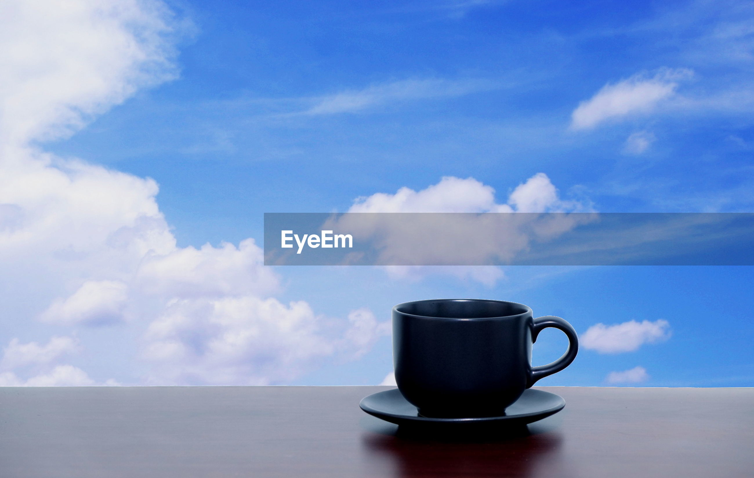COFFEE CUP ON GLASS TABLE AGAINST BLUE SKY