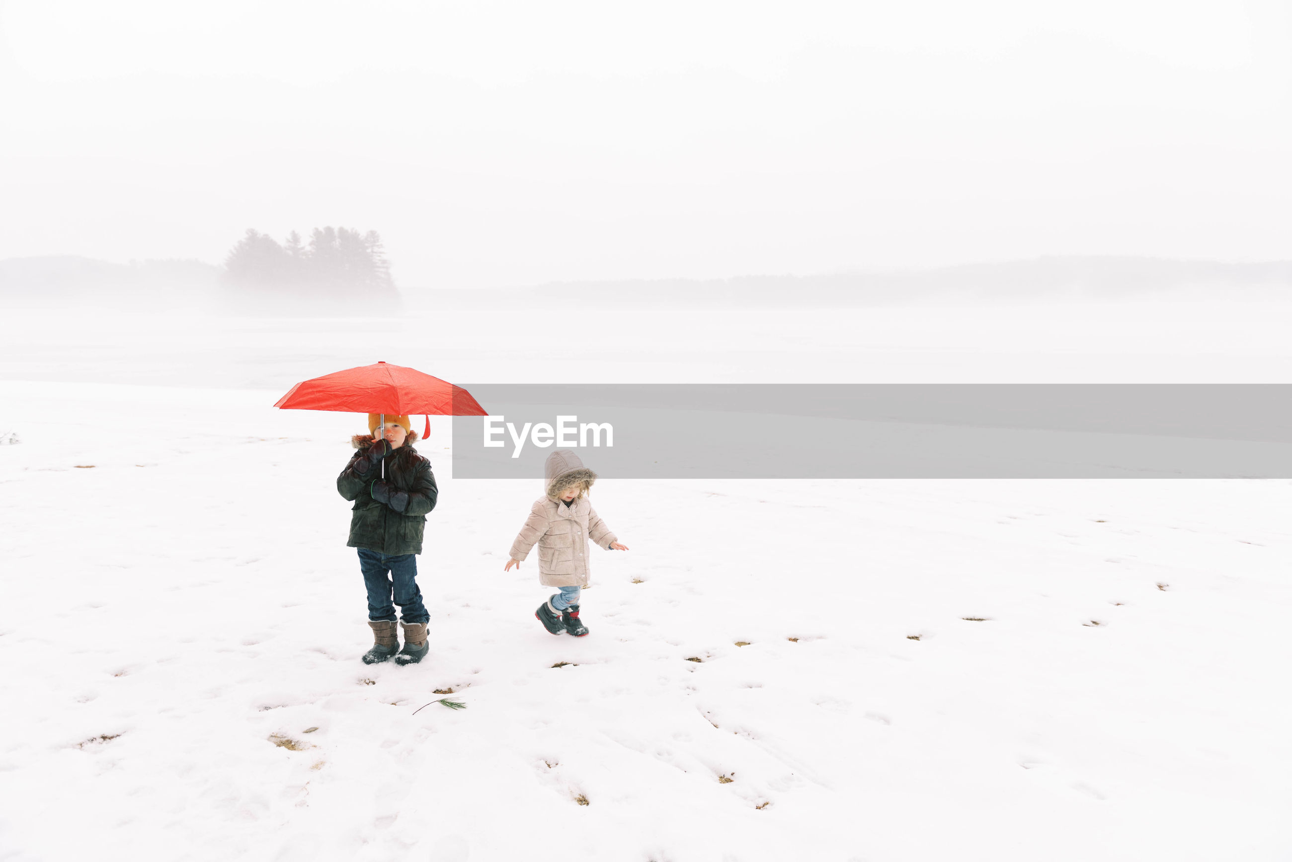REAR VIEW OF WOMEN ON SNOW COVERED LAND