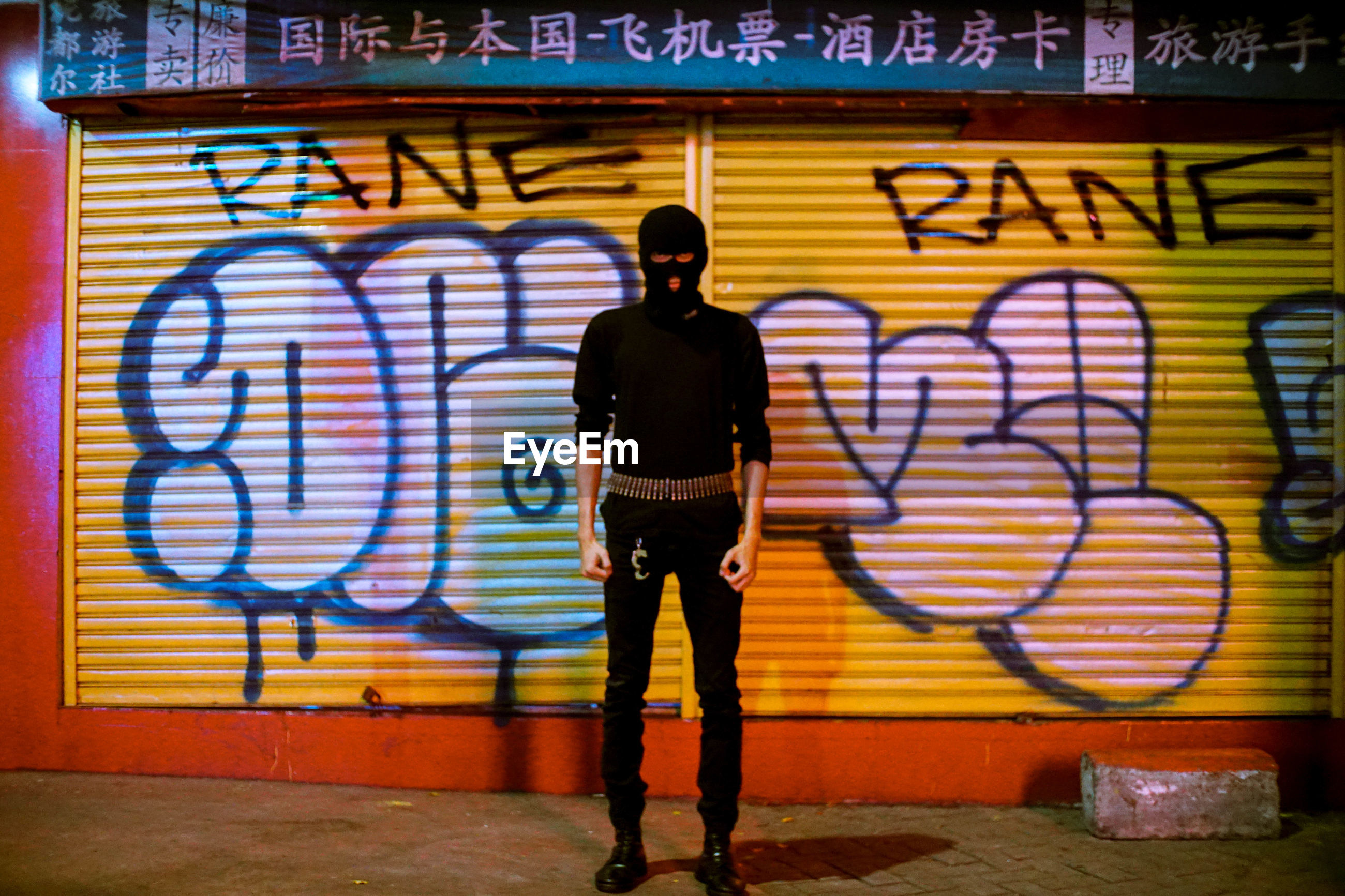 FULL LENGTH REAR VIEW OF MAN STANDING AGAINST GRAFFITI WALL