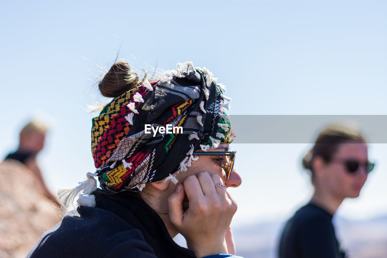 Side view of woman with hands on cheek against sky