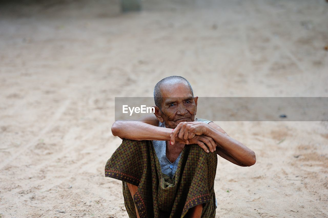 Portrait Of Smiling Senior Man Sitting Outdoors