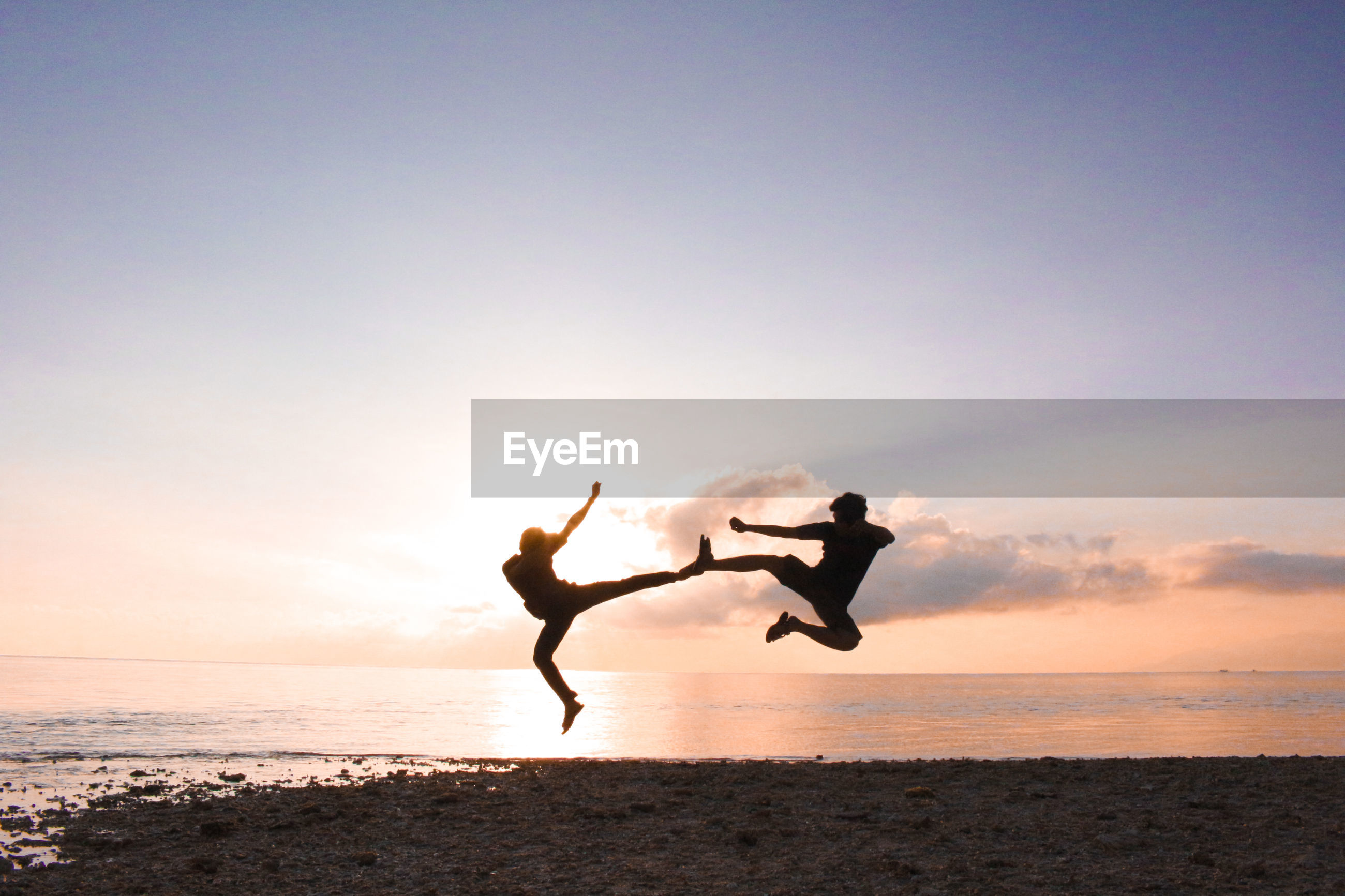 Silhouette men jumping at beach against sky during sunset
