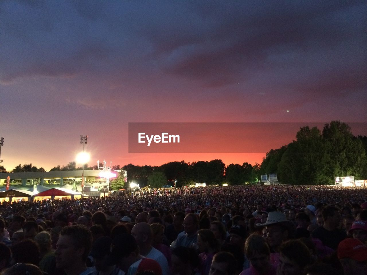 large group of people, crowd, music festival, music, illuminated, sky, real people, night, arts culture and entertainment, sunset, lifestyles, cloud - sky, women, outdoors, leisure activity, enjoyment, men, togetherness, stage - performance space, popular music concert, performance, audience, nature, tree, city, people, adult