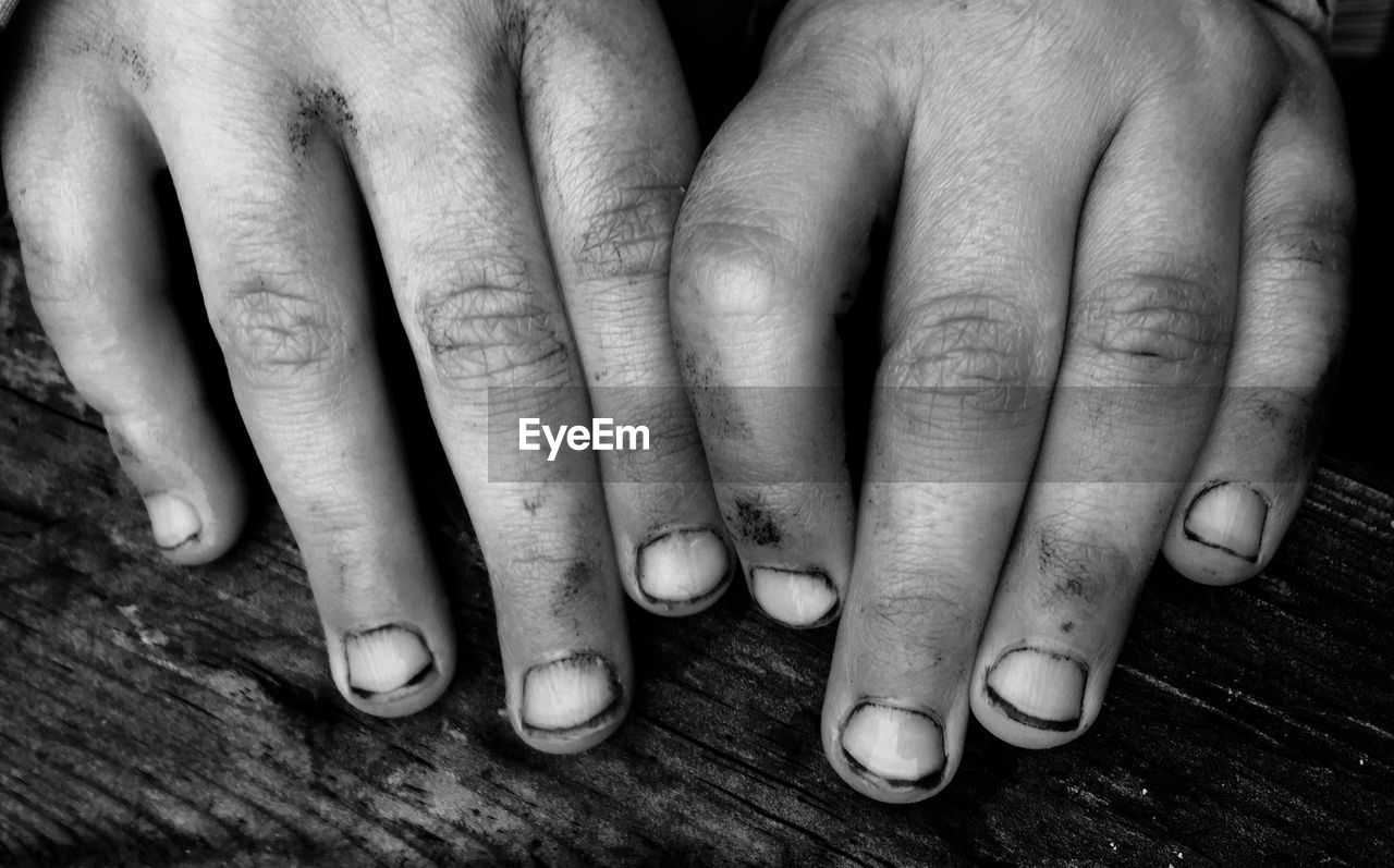 Cropped image of dirty hands on wood