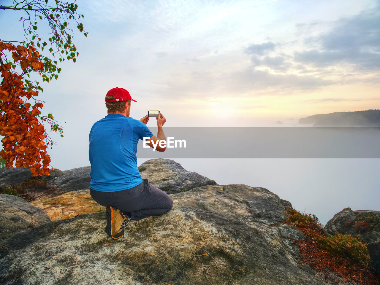 REAR VIEW OF MAN ON ROCKS AT SHORE AGAINST SKY