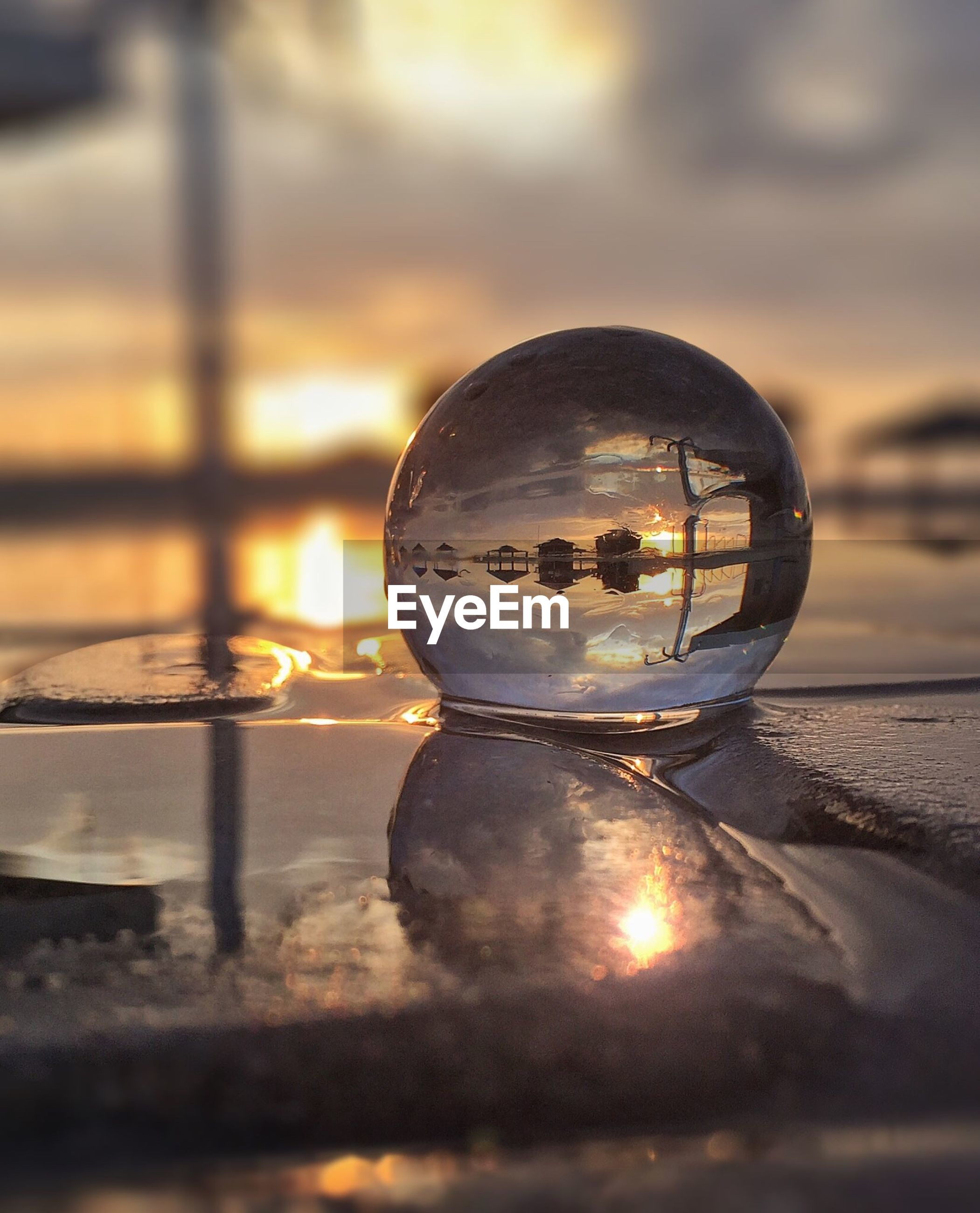 Close-up of crystal ball in water at sunset