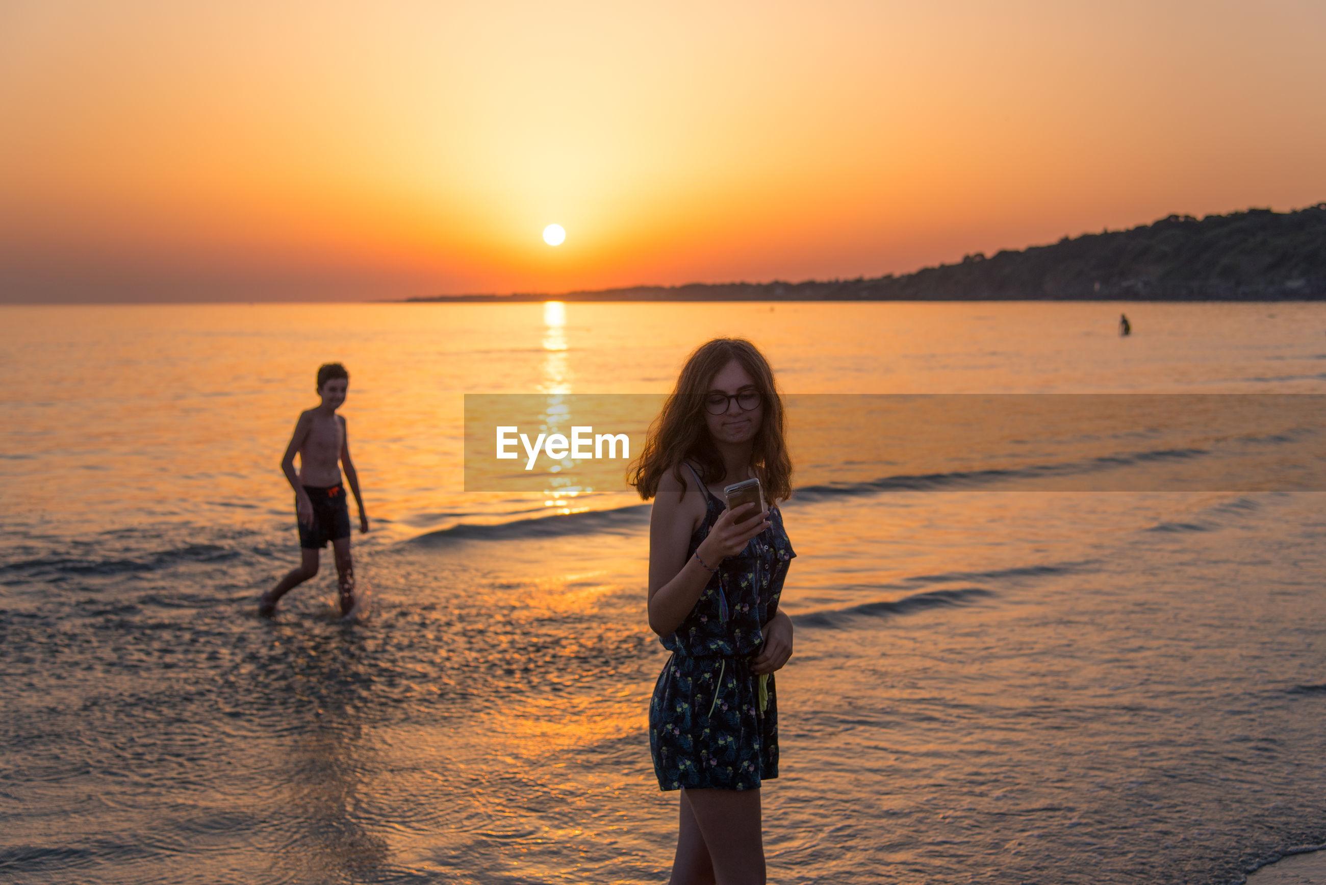 Teenage girl using phone near boy walking at beach during sunset