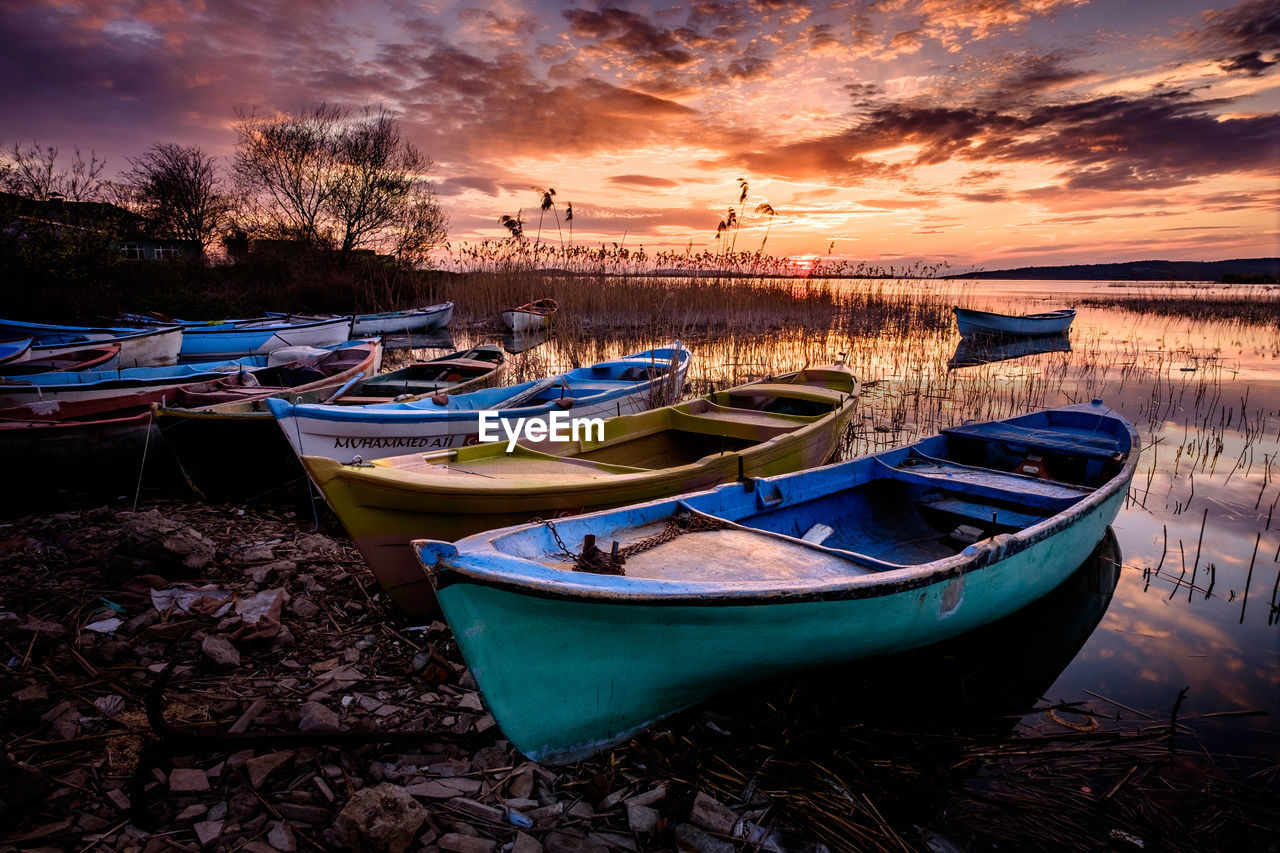 nautical vessel, moored, water, mode of transportation, sky, transportation, cloud - sky, sunset, nature, tranquility, land, beach, scenics - nature, no people, tranquil scene, beauty in nature, lake, rowboat, plant, outdoors, fishing boat, recreational boat