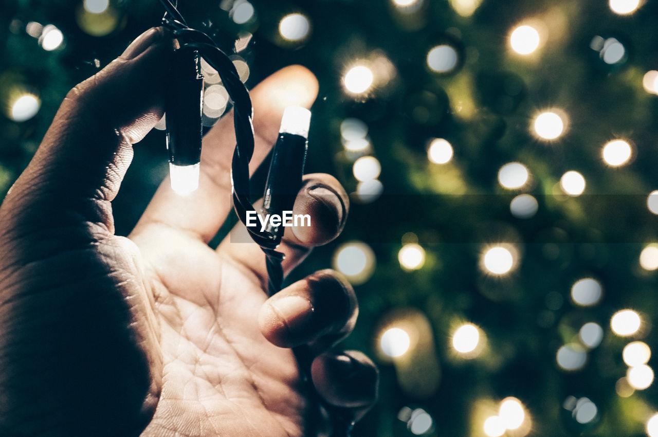 Close-Up Of Hand Holding Illuminated Christmas Tree At Night