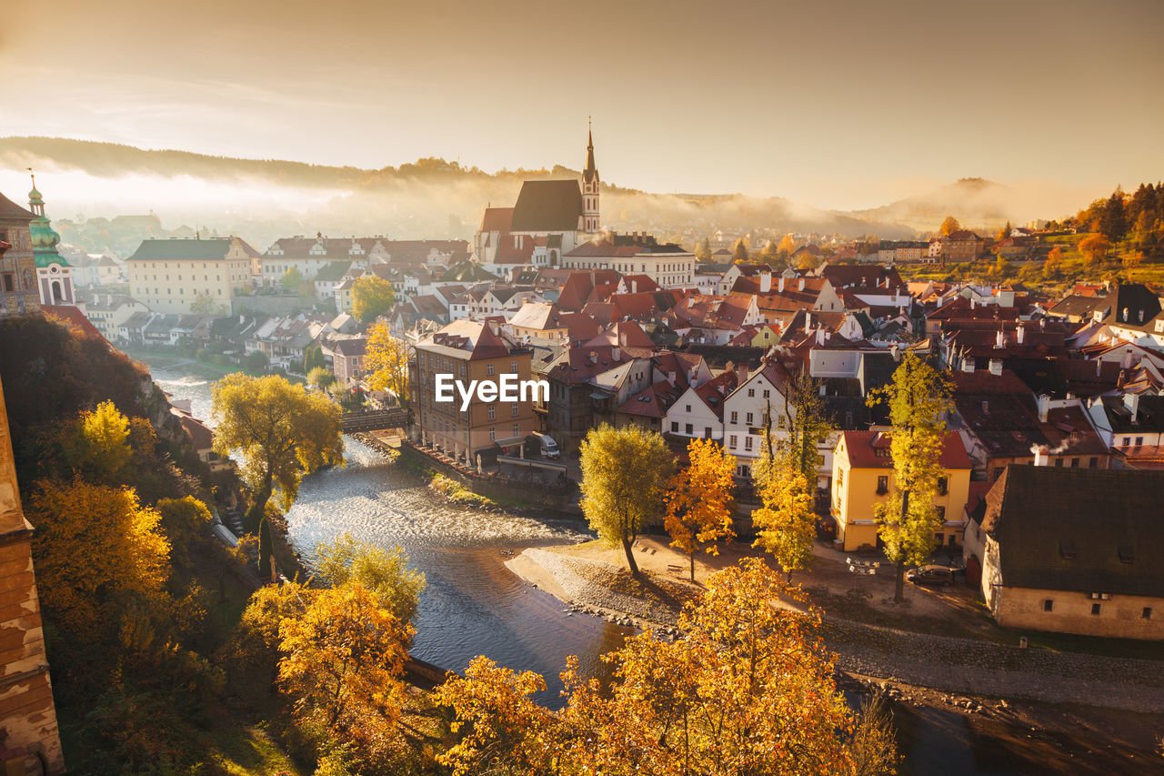 Townscape by river against sky during autumn