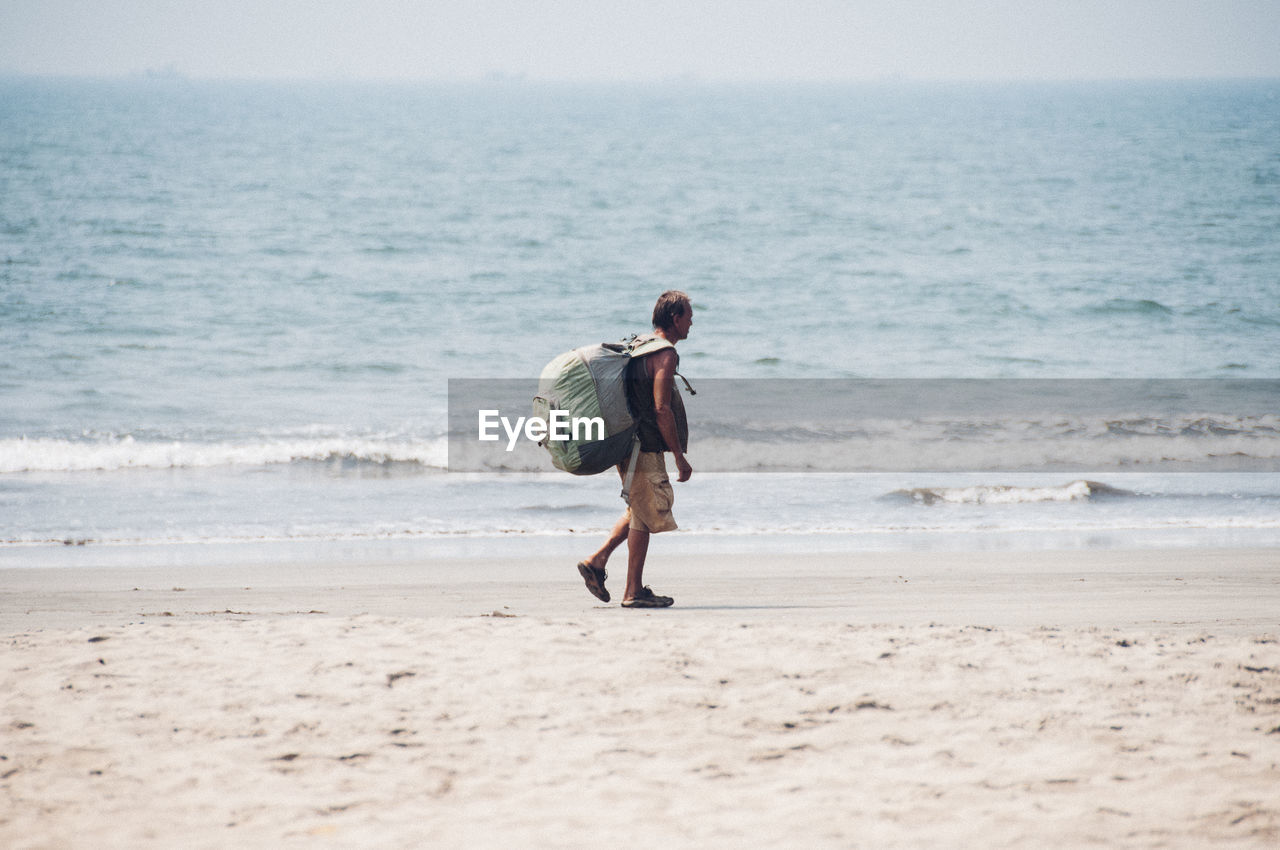 FULL LENGTH OF MAN WALKING ON BEACH AGAINST SKY