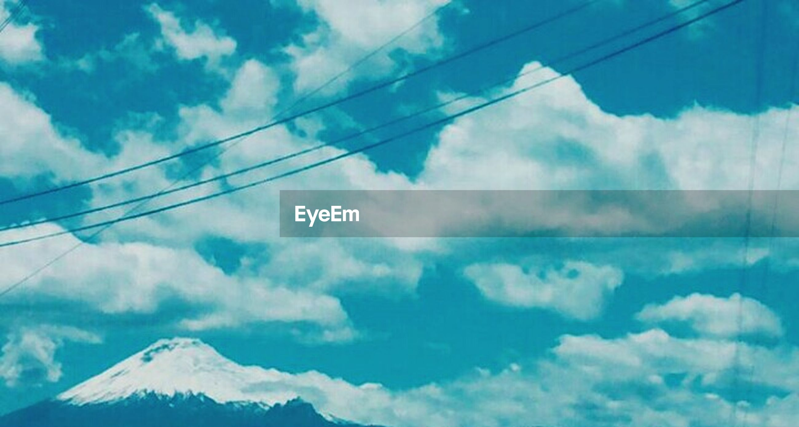 sky, cloud - sky, power line, low angle view, mountain, cable, connection, cloudy, cloud, electricity, tranquility, scenics, beauty in nature, blue, tranquil scene, nature, power supply, electricity pylon, mountain range, weather