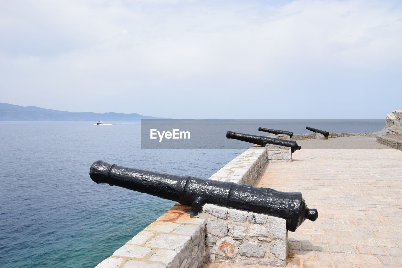 water, sky, sea, weapon, cannon, scenics - nature, nature, day, tranquil scene, metal, no people, outdoors, cloud - sky, beauty in nature, history, the past, security, non-urban scene, war, hand-held telescope