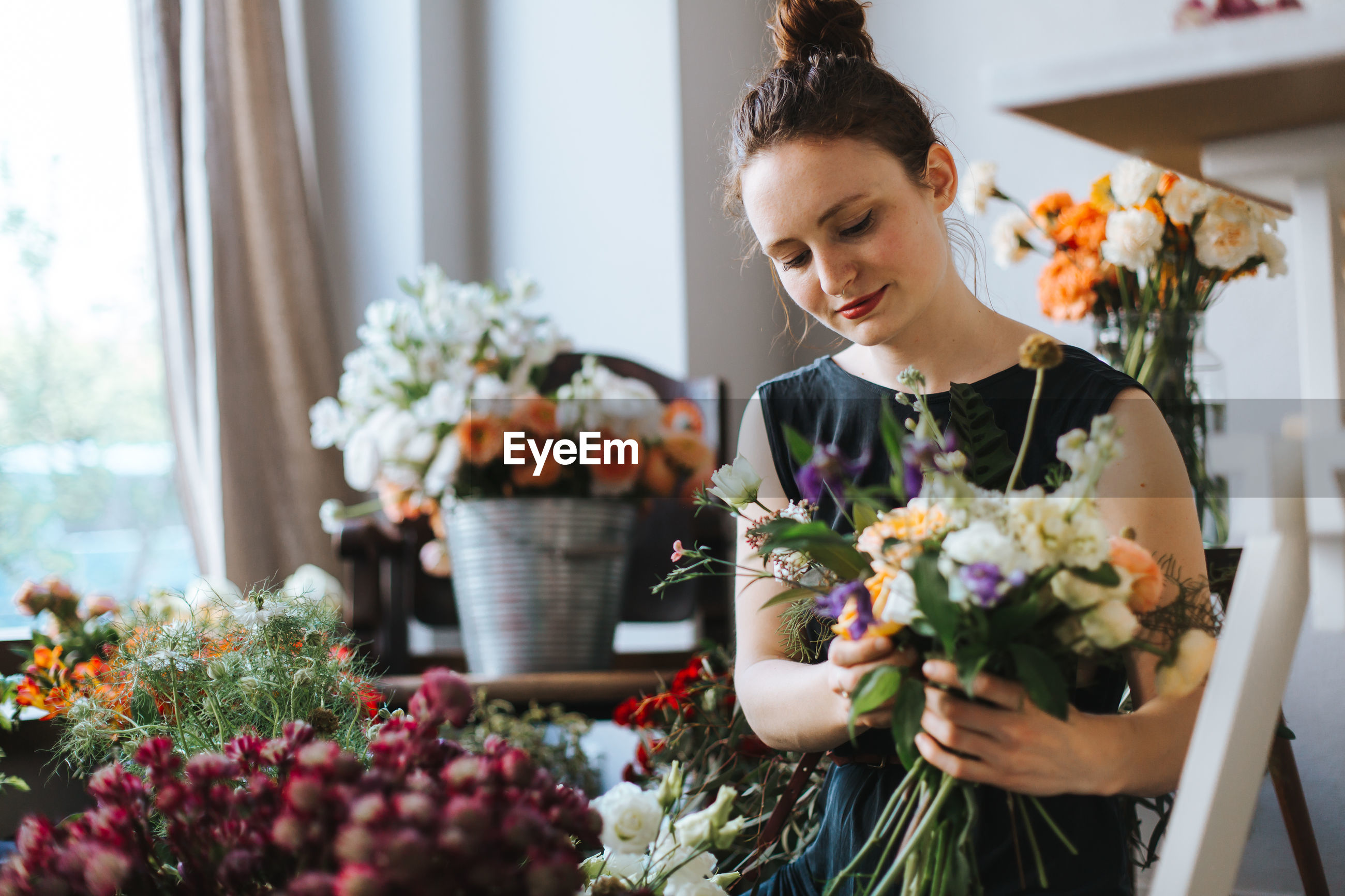 Woman arranging flowers in shop