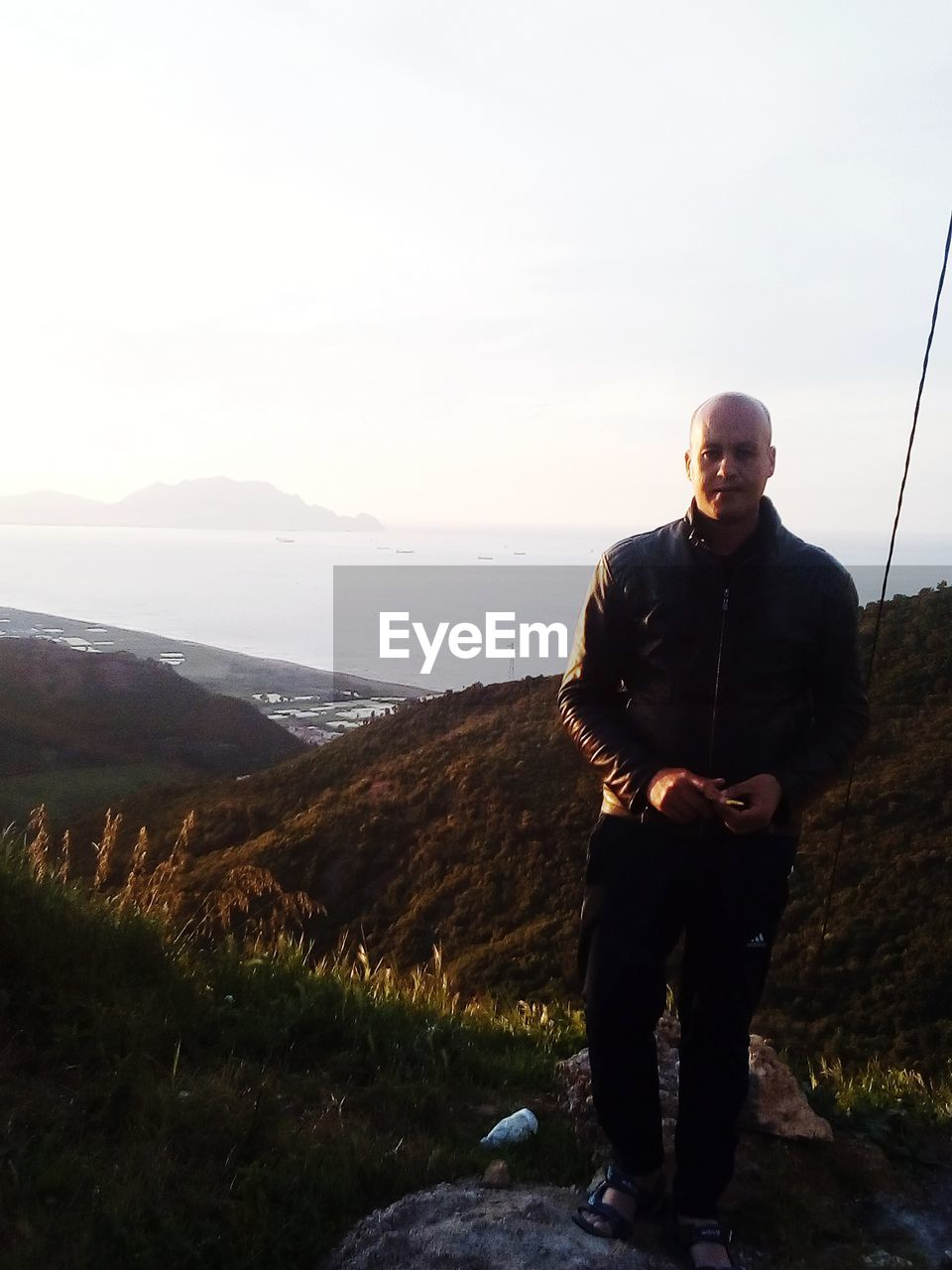 Portrait of bald man standing on mountain against sky