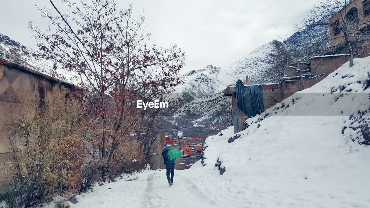 snow, winter, cold temperature, weather, nature, mountain, real people, beauty in nature, tree, one person, outdoors, rear view, walking, warm clothing, snowcapped mountain, sky, day, full length, men, architecture, leisure activity, built structure, scenics, lifestyles, bare tree, people